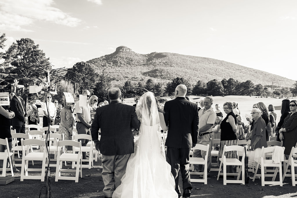 Black and White of Bride getting walked down aisle at Pilot Knob Country Club. Wedding Photography by Party of Two Photography.