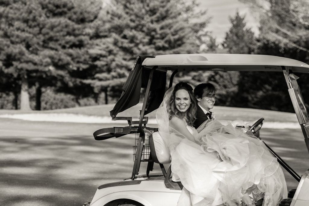 Black and White photo of bride and groom driving away in golf cart at Pilot Knob Country Club. Wedding Photography by Party of Two Photography.