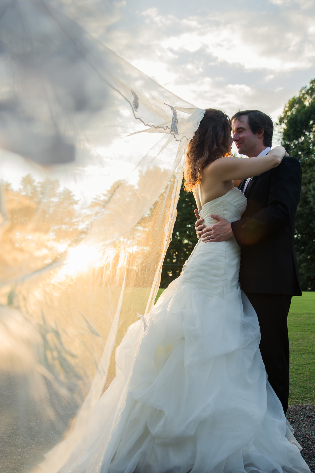 Bride and Groom Kissing with veil during sunset at Pilot Knob Country Club. Wedding Photography by Party of Two Photography.