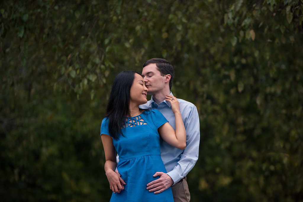 Couple holding each other in front of trees in Freedom Park in Charlotte, North Carolina. Engagement Photography by Party of Two Photography.