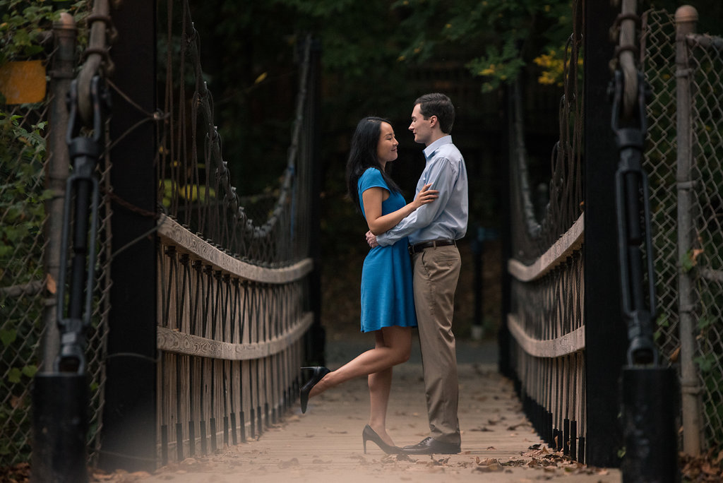Cute engagement photo idea of standing on bridge in Freedom Park in Charlotte, North Carolina. Engagement Photography by Party of Two Photography.