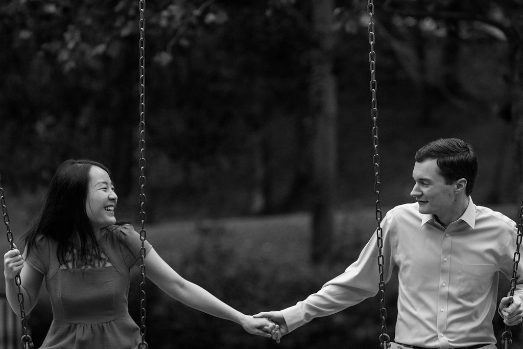 Black and white photo of couple swinging in Freedom Park in Charlotte, North Carolina. Engagement Photography by Party of Two Photography.