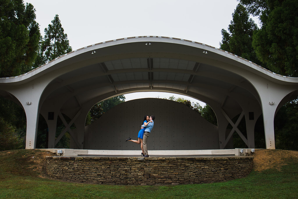 Fun engagement photo of guy lifting girl in an amphitheater in Freedom Park in Charlotte, North Carolina. Engagement Photography by Party of Two Photography.