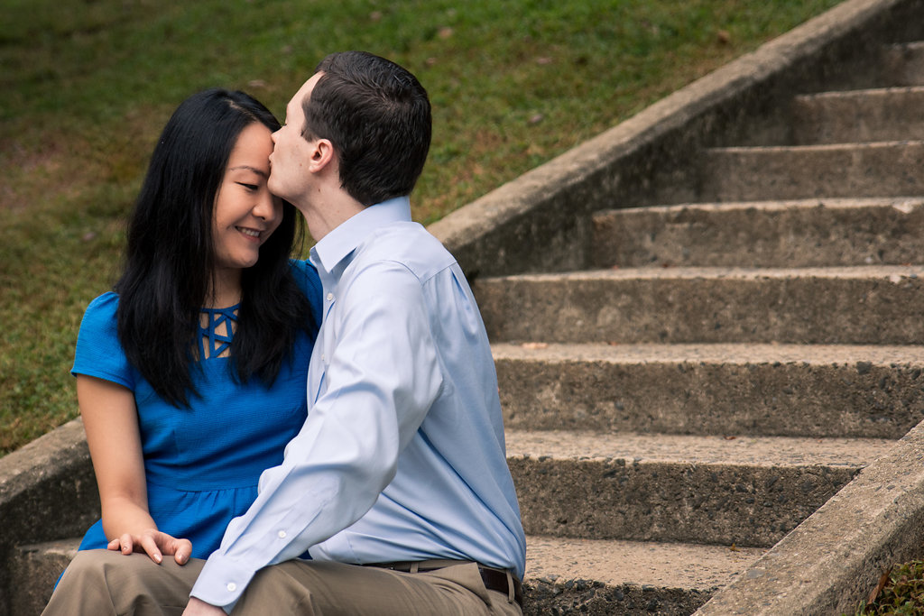 Sweet engagement photography of forehead kiss on stairs in Freedom Park in Charlotte, North Carolina. Engagement Photography by Party of Two Photography.