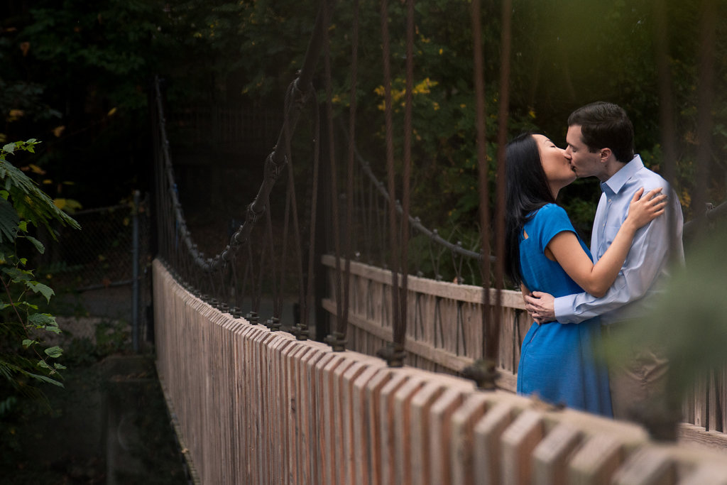 Sweet engagement photo of couple kissing on bridge in Freedom Park in Charlotte, North Carolina. Engagement Photography by Party of Two Photography.