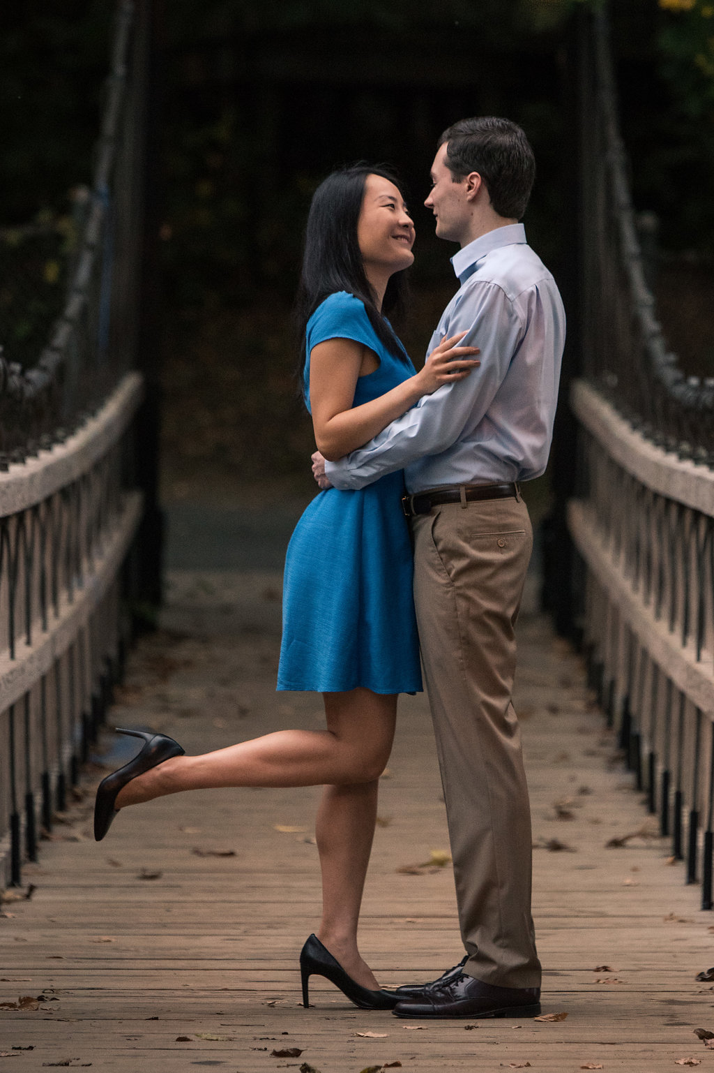 Couple standing on bridge holding eachother in Freedom Park in Charlotte, North Carolina. Engagement Photography by Party of Two Photography.