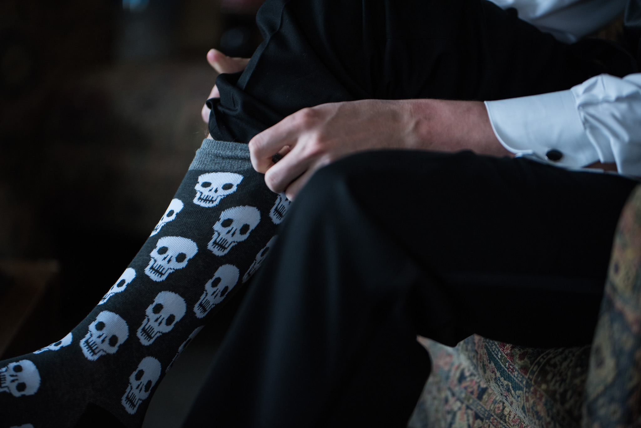 Groom getting ready with special socks in Pilot Knob Country Club. Wedding Photography by Party of Two Photography.