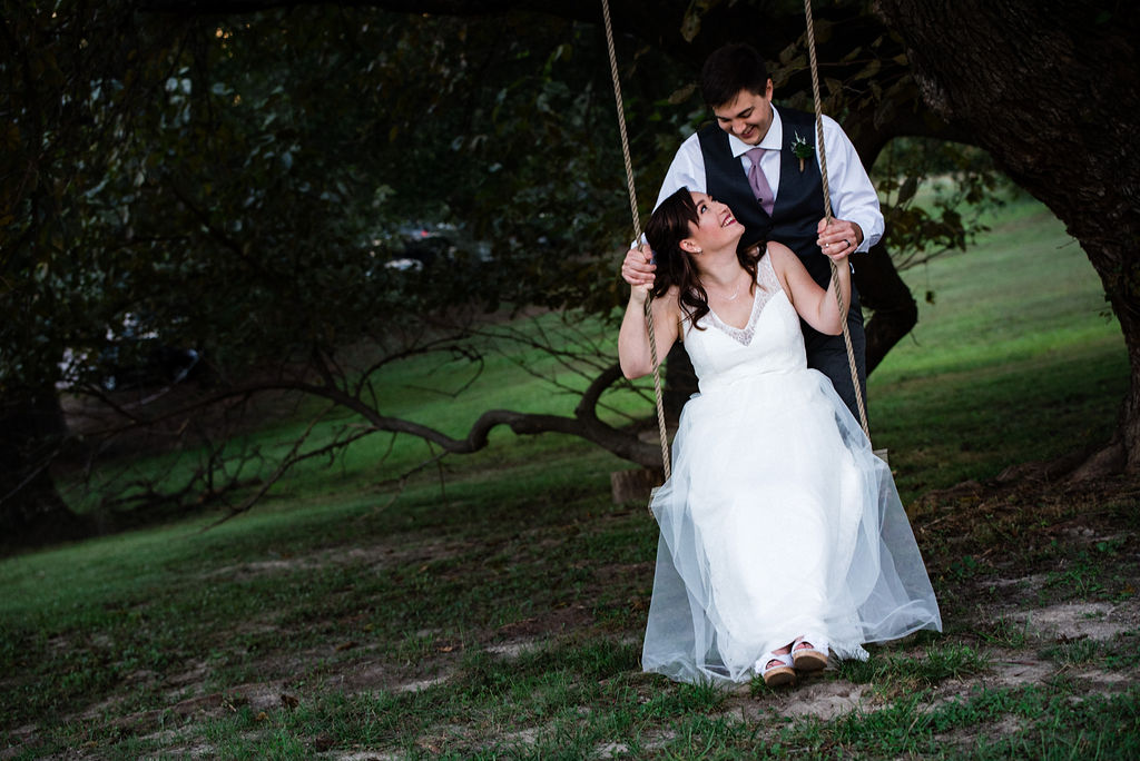 Bride and Groom Sunset Portraits on Swing at The Oaks at Salem Wedding in Apex, NC by Charlotte Wedding Photographers