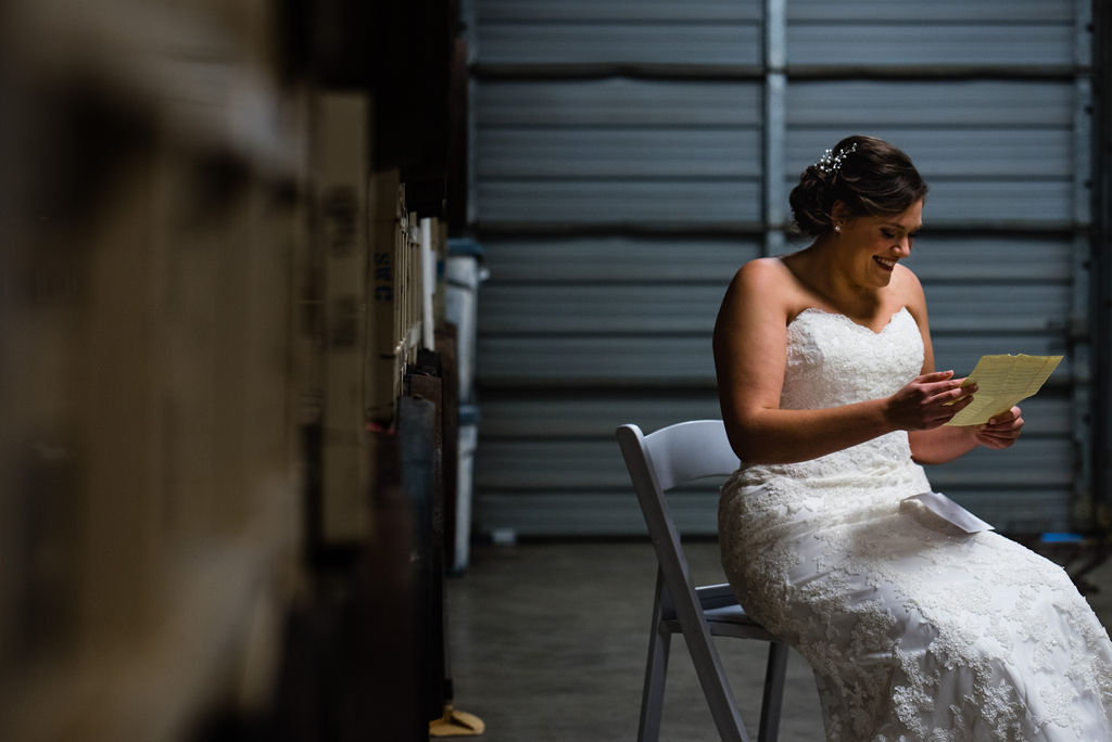 Bride Reading Letter at Triple C Barrel Room by Charlotte Wedding Photographers