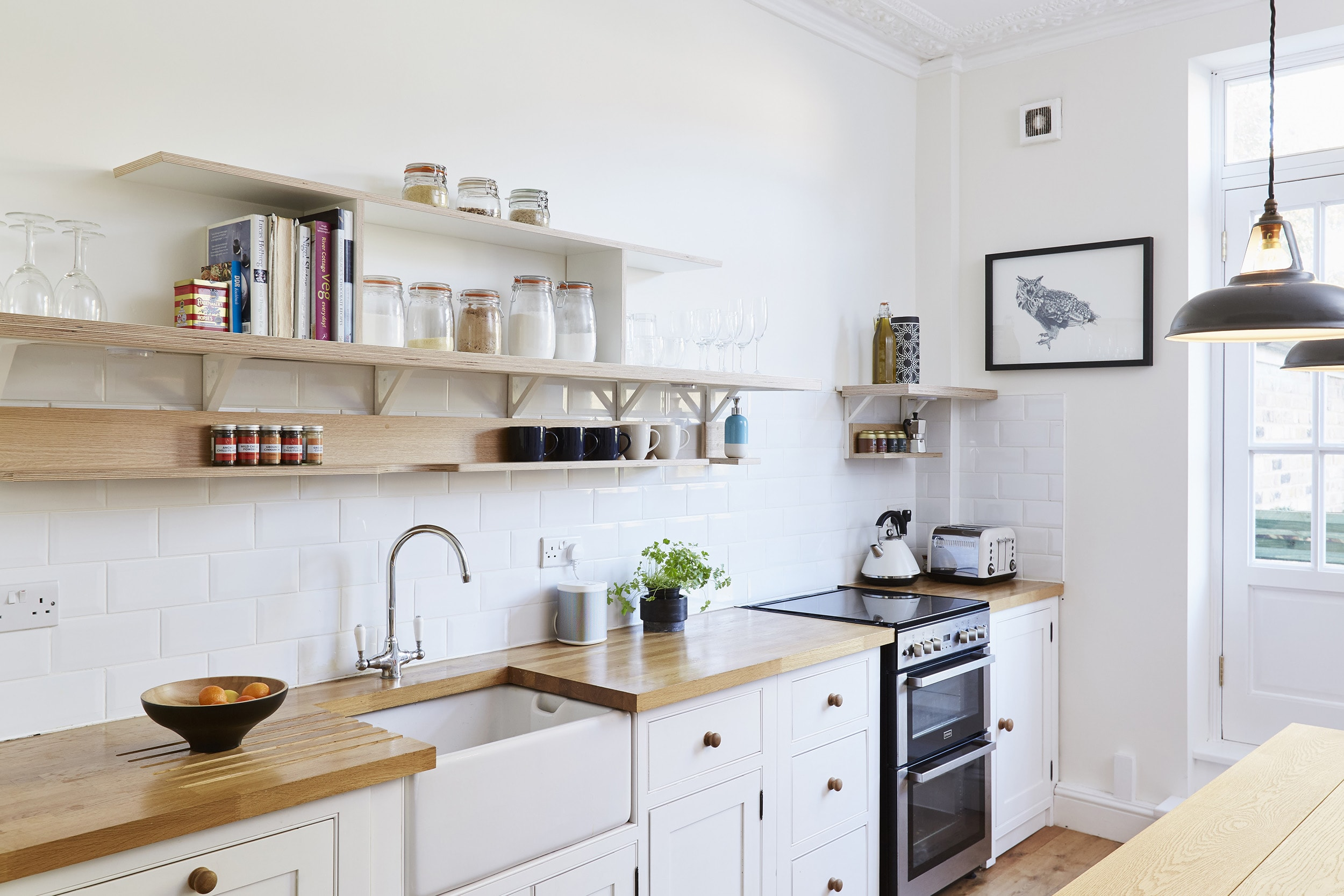 Lozi's bespoke plywood shelving system was designed to fit around the existing kitchen design, creating extra storage that is easily accessible. The use of open plan shelves rather than cabinets has kept the space bright and airy, allowing light to flow between the kitchen and living room.