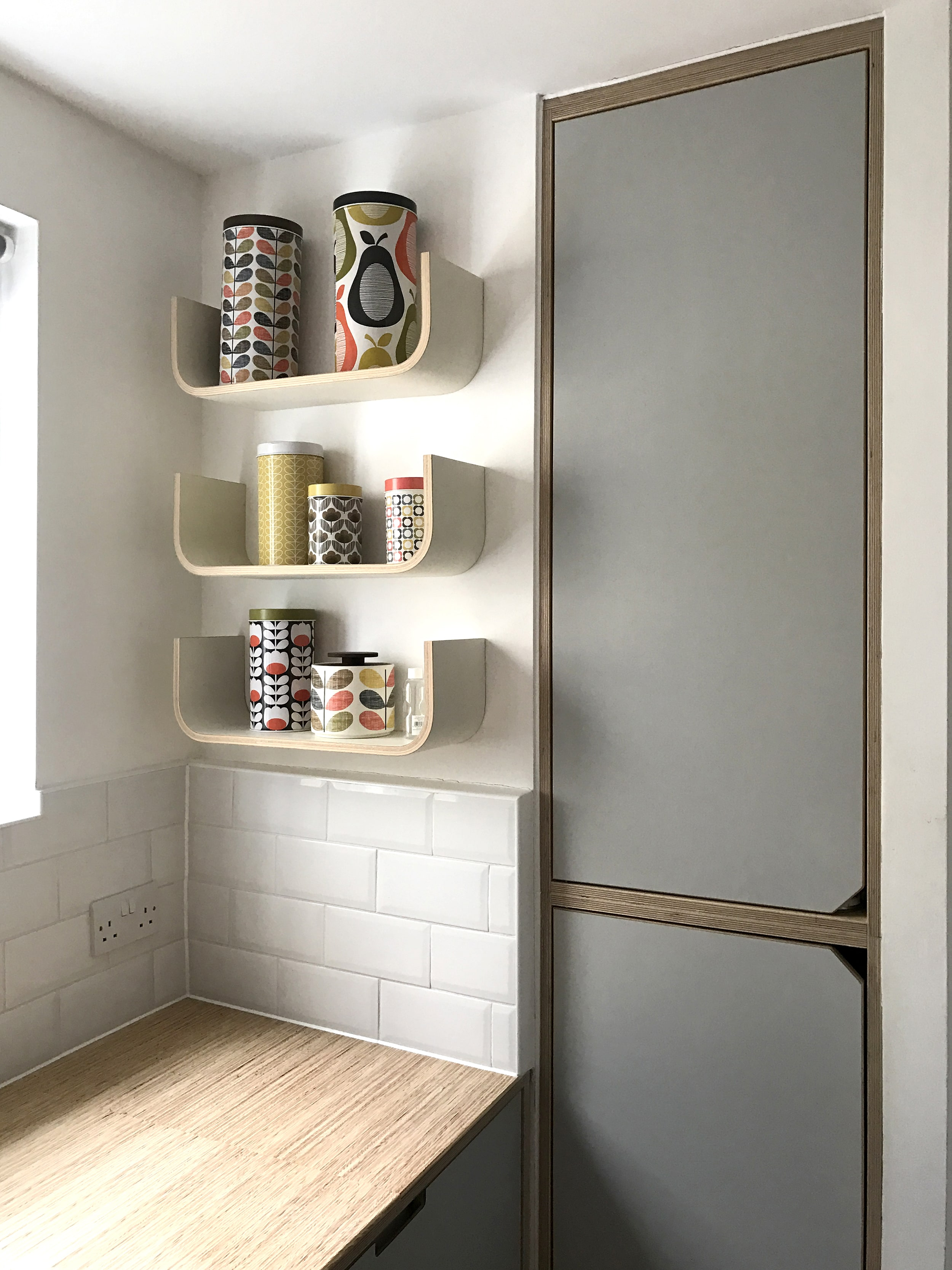 A long empty space left after changing the layout of the bathroom behind it is turned into a storage cupboard, with space for a hoover and brooms.