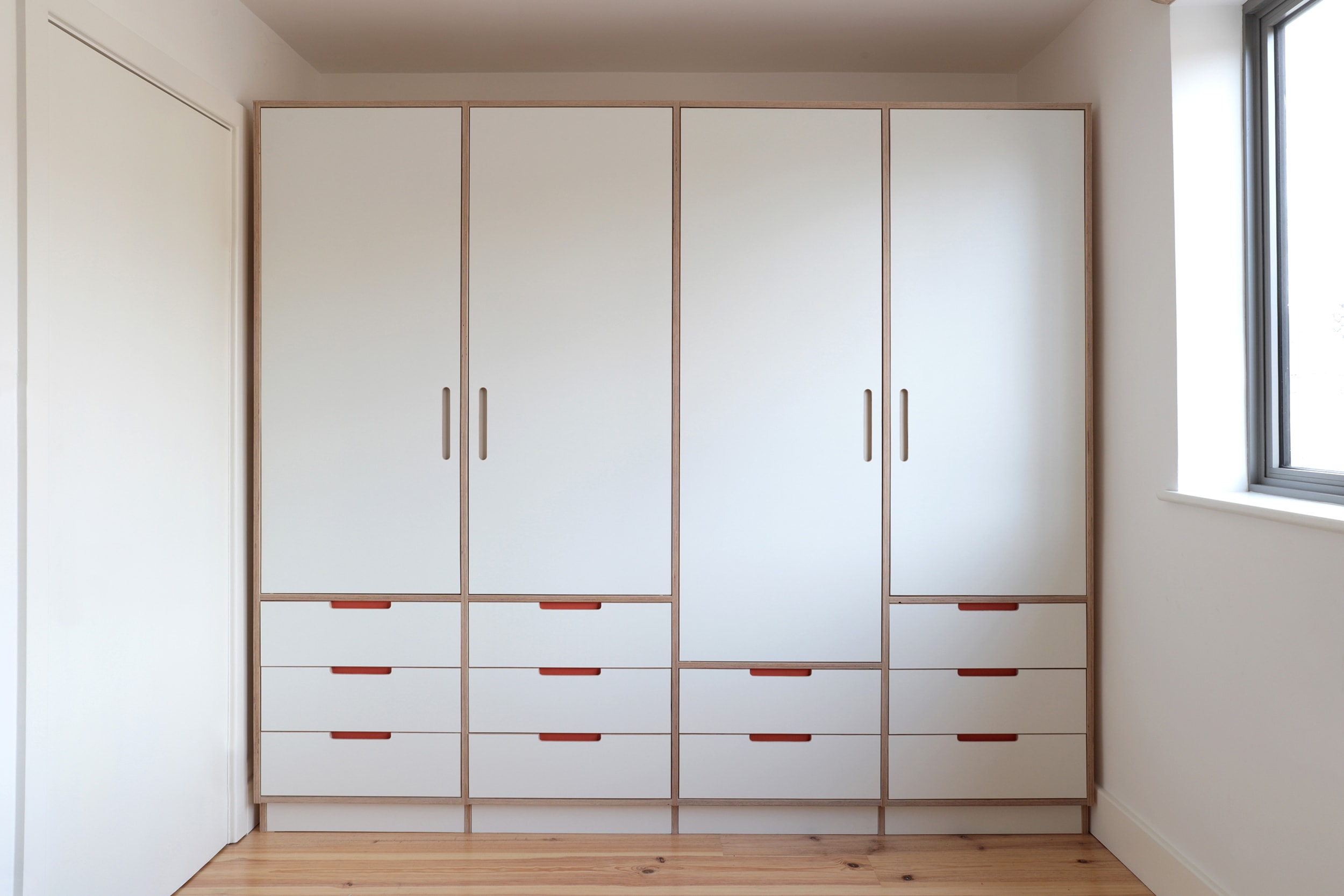 Ilaria's clean bespoke plywood kids wardrobe designed by Lozi in her home in East London