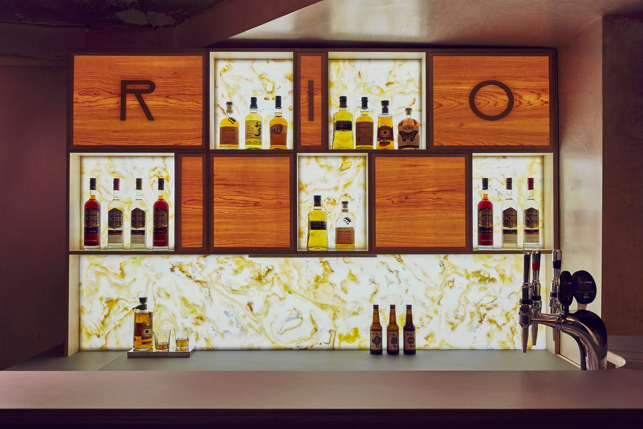 The back lit bar, inspired by the Gold Room from the Shining, showcases the selection of spirits.