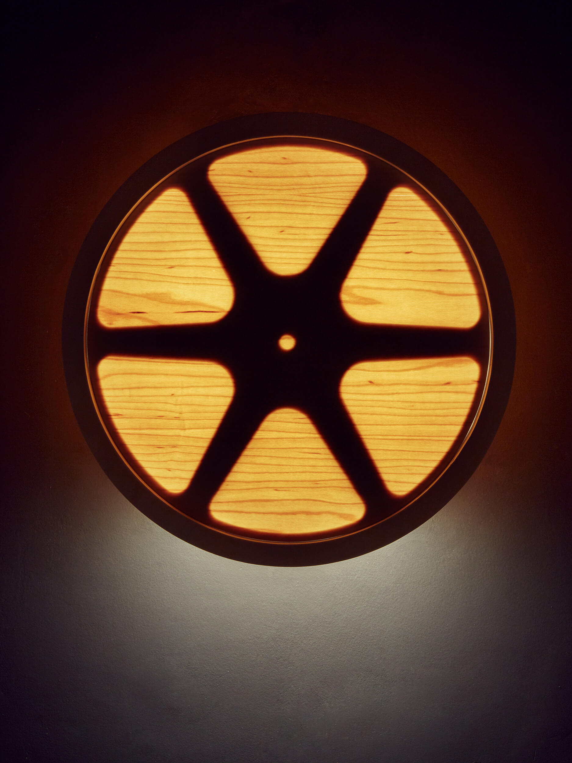 A close up of the wall mounted film reel Sunset lamp