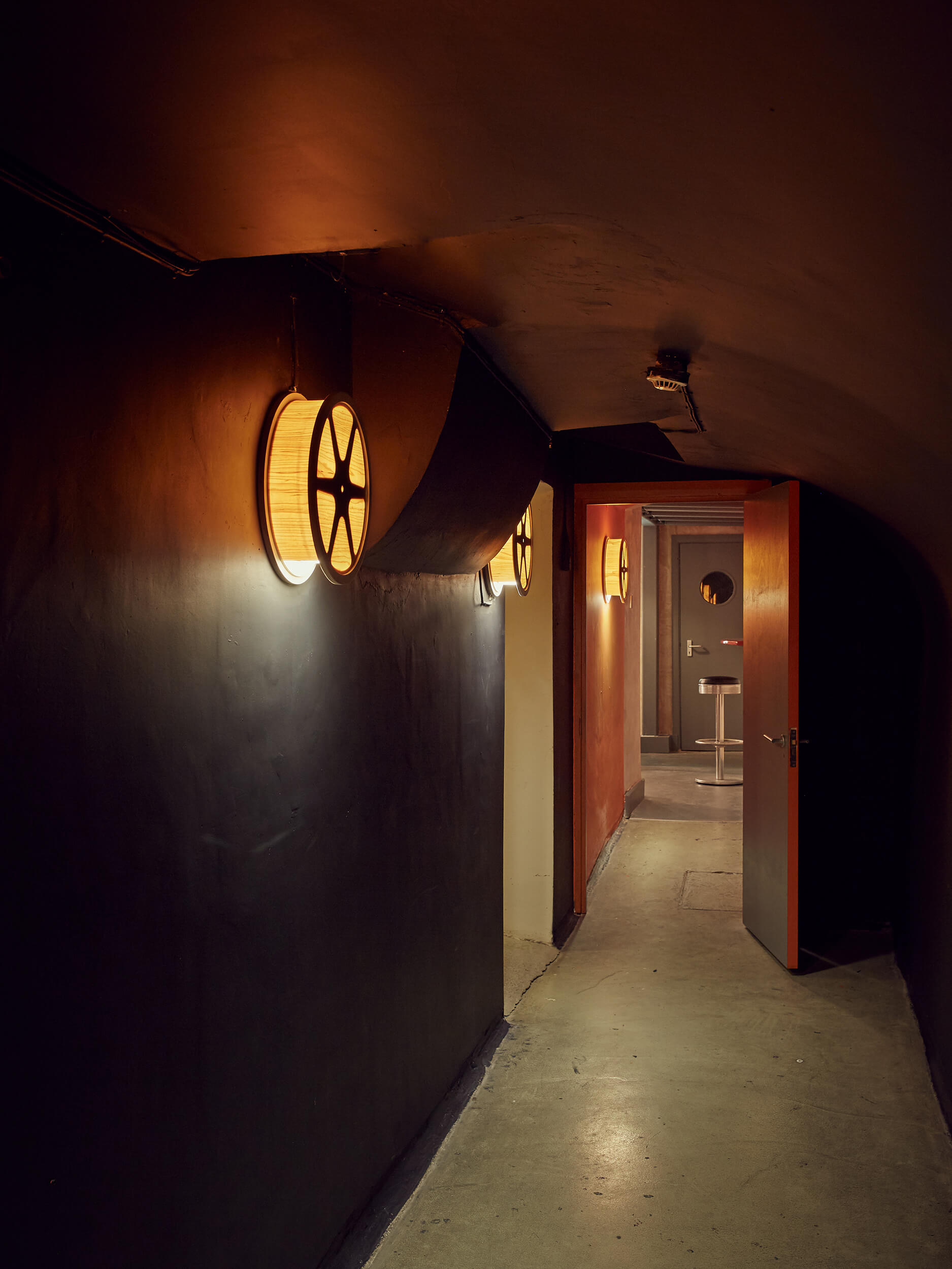 The corridor leading to the bar, illuminated with film reel sunset lamps.