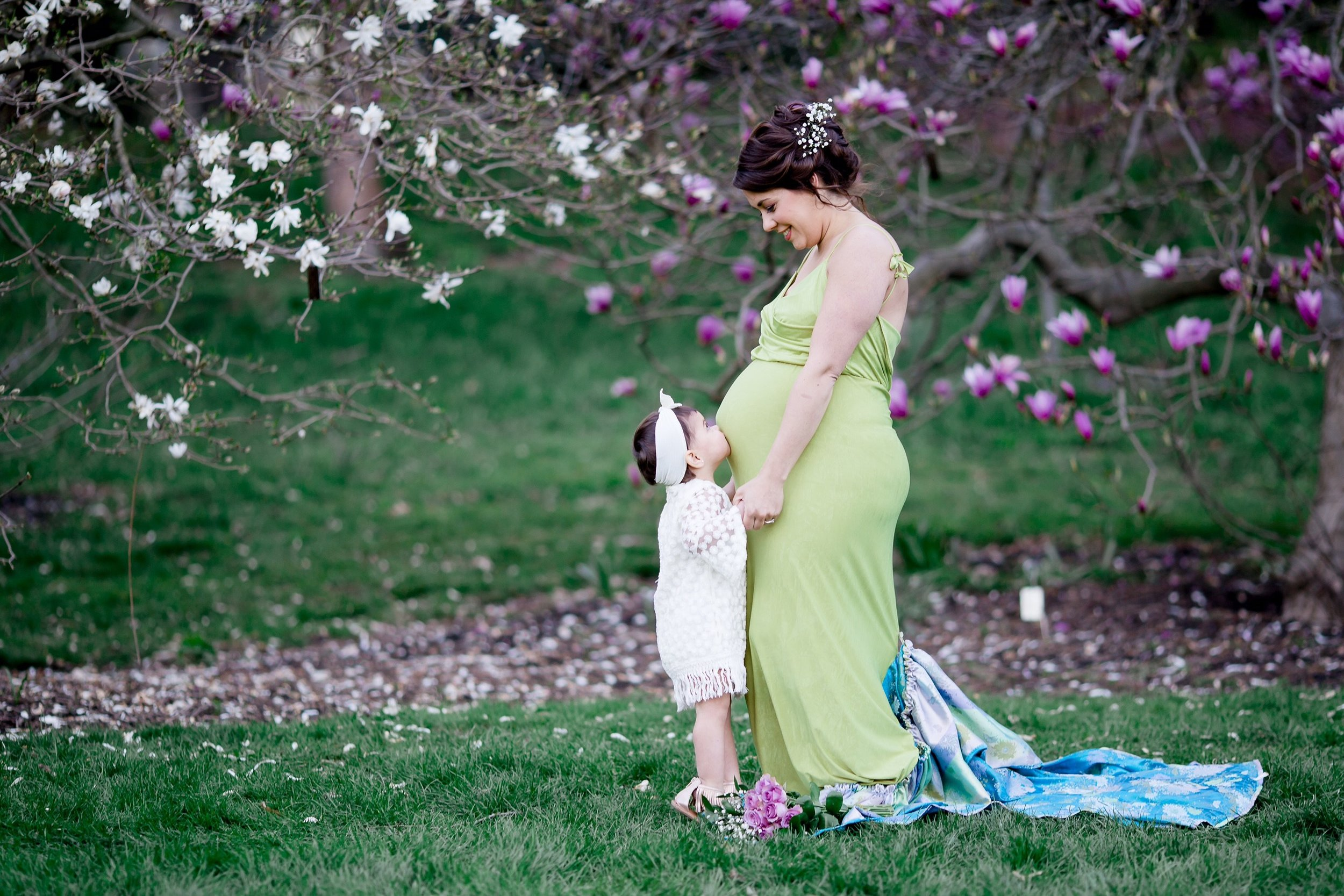 pregnant mom with daughter kissing belly outdoors with spring flowers
