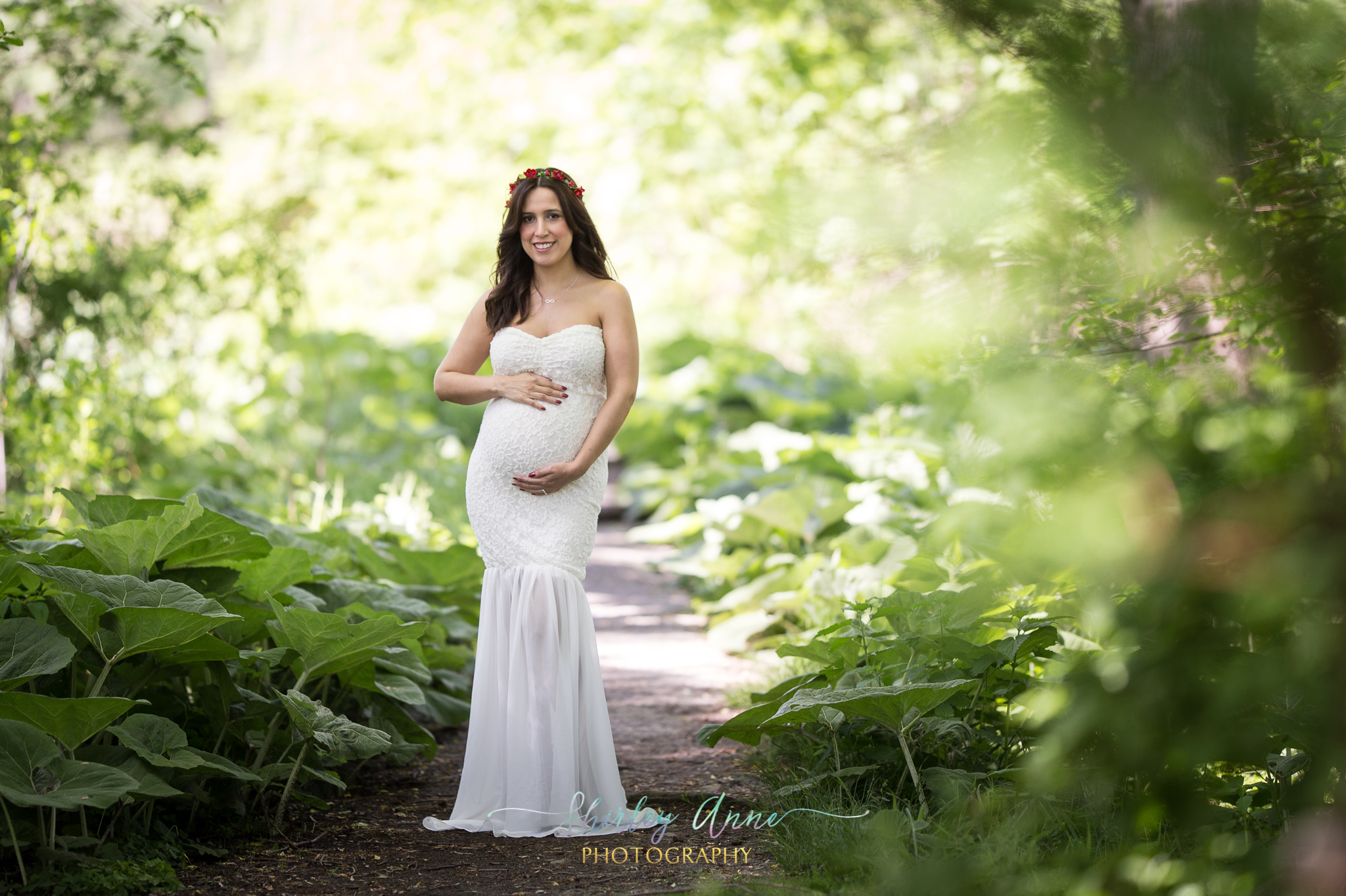 expecting mom in green forest during outdoor session in maternity gown