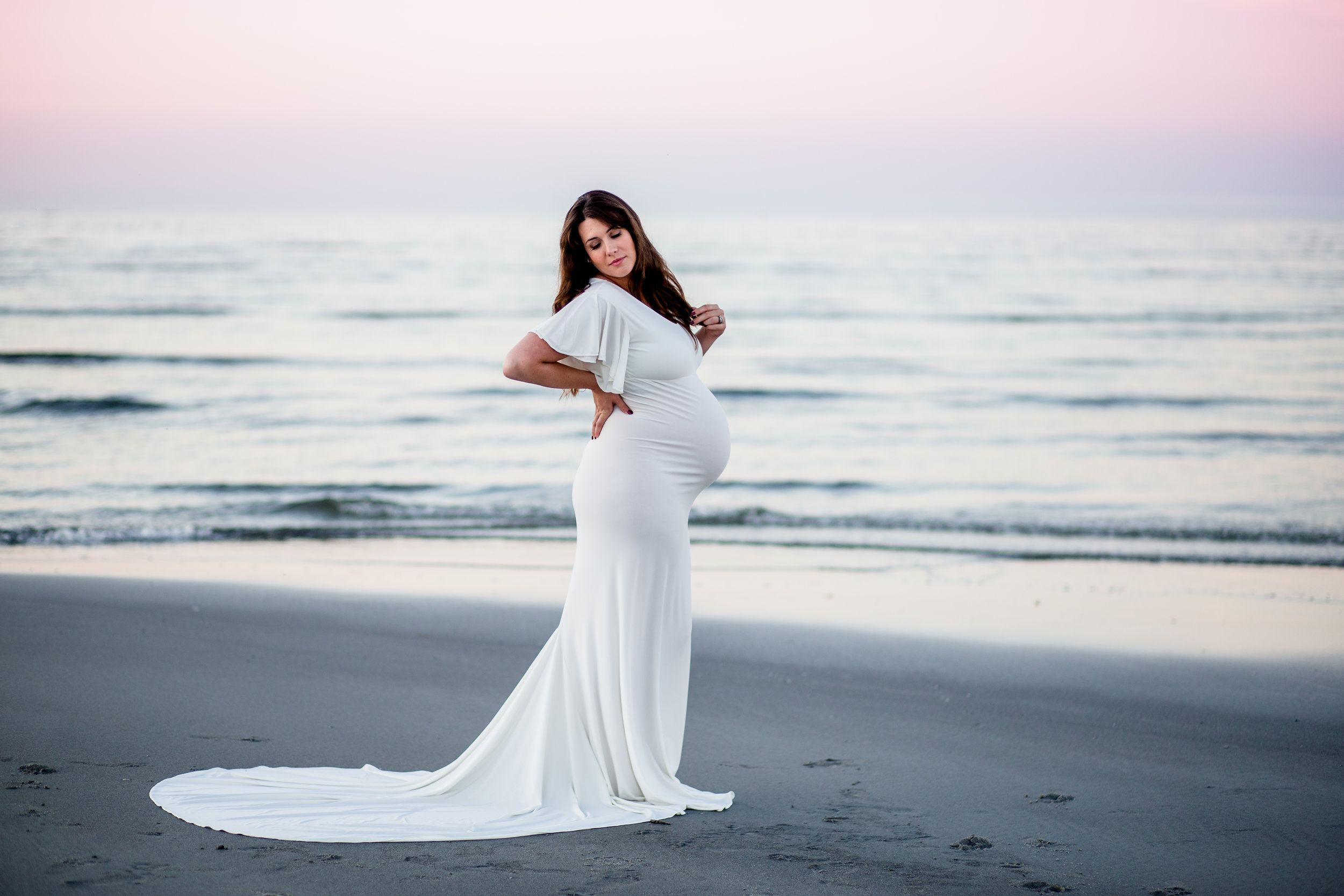 beach maternity session with colorful sky and designer dress