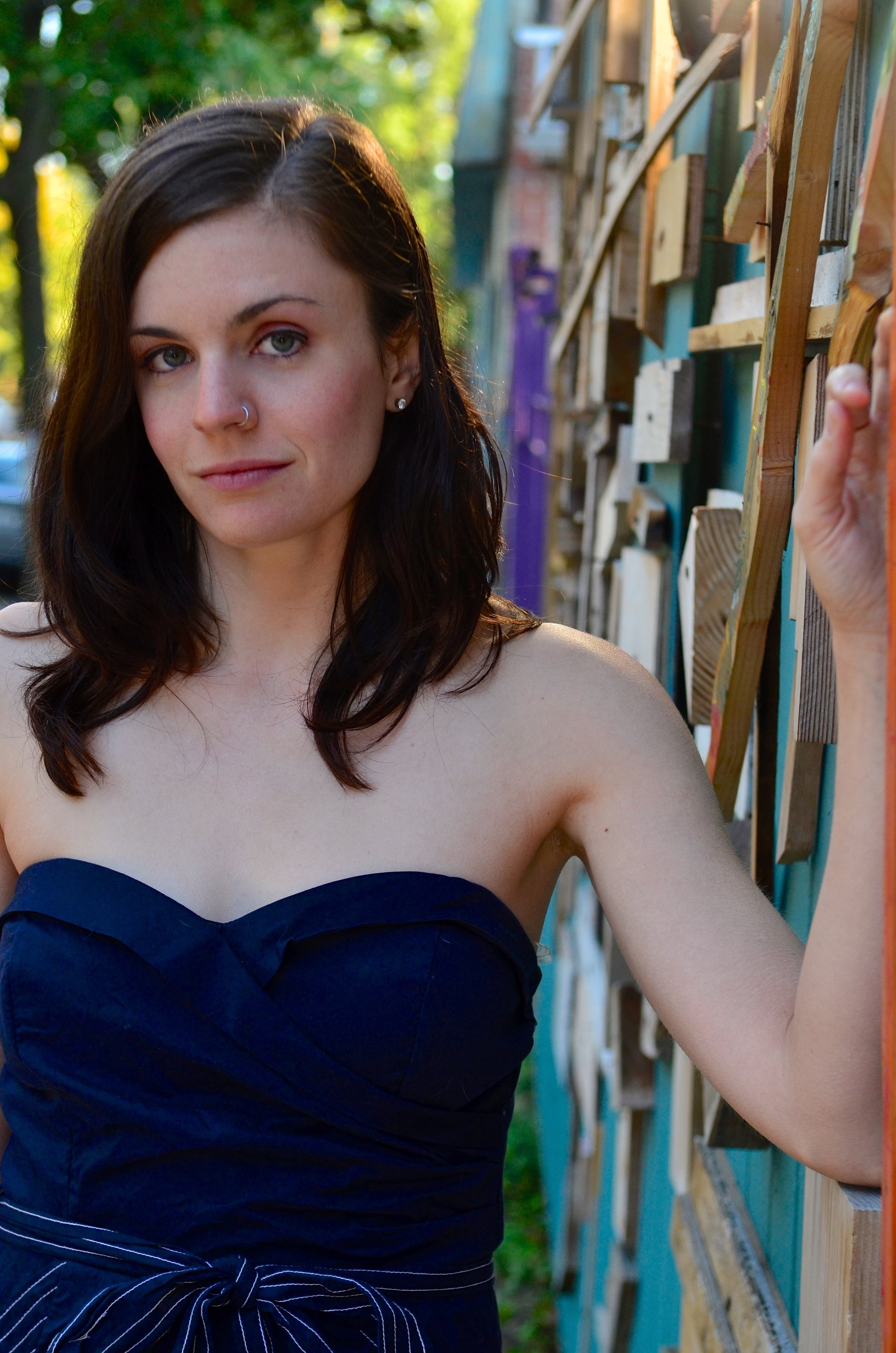 Photo by Jeff White:  A photo of Christine. She is fair-skinned and her skin has a pink hue. Her body is lean and she is dressed in a navy blue strapless dress. She is in her mid 20's in this photo. Her hand is propped on a colorful wall she leans against, a half smirk on her face as she gazes directly at the camera. Her brown hair falls past her shoulders and she has a nose ring and arched eyebrows. Behind her a residential street shines green through the summer leaves.