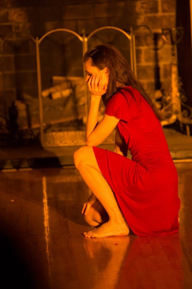 Photo by Roberto Martinez:   Christine kneels on a wooden floor, one knee tucked under. Her elbow rests on her other knee and her head rests in her hand. Her eyes are downcast, pensive. She is thin, wearing a red dress with her long brown hair falling to her back. Her reflection shines on the polished floor and behind her a fireplace is stocked with wood, but not lit. The scene is cast with an orange tint.