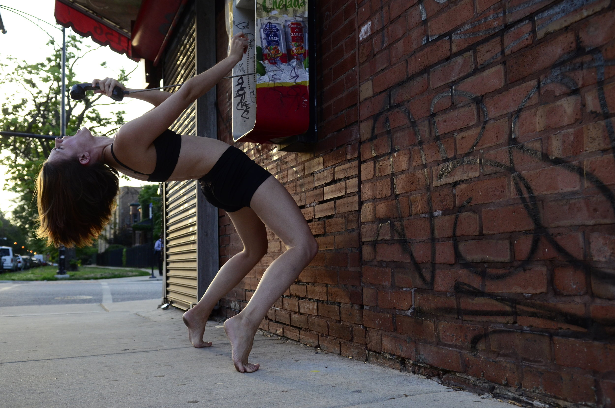 Photo by Jeff White:  Christine is at a payphone on a brick wall dressed in black shorts and a sports bra. The phone and wall are graffitied. She is arching back, one had inserting a coin into the payphone, other hand gripping the receiver away from her face, mouth open as if yelling. In the distance a residential street shines soft light though her brown hair which is loose.