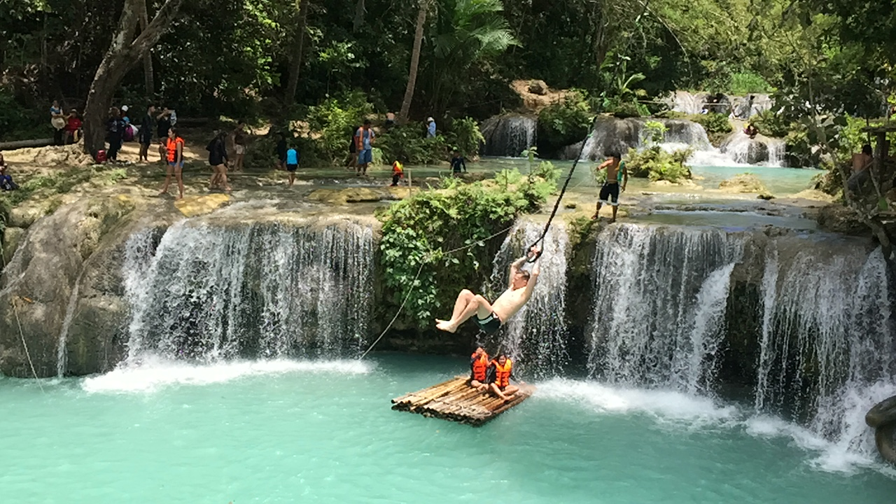 James swinging into the piercing turquoise of Cambugahay Falls