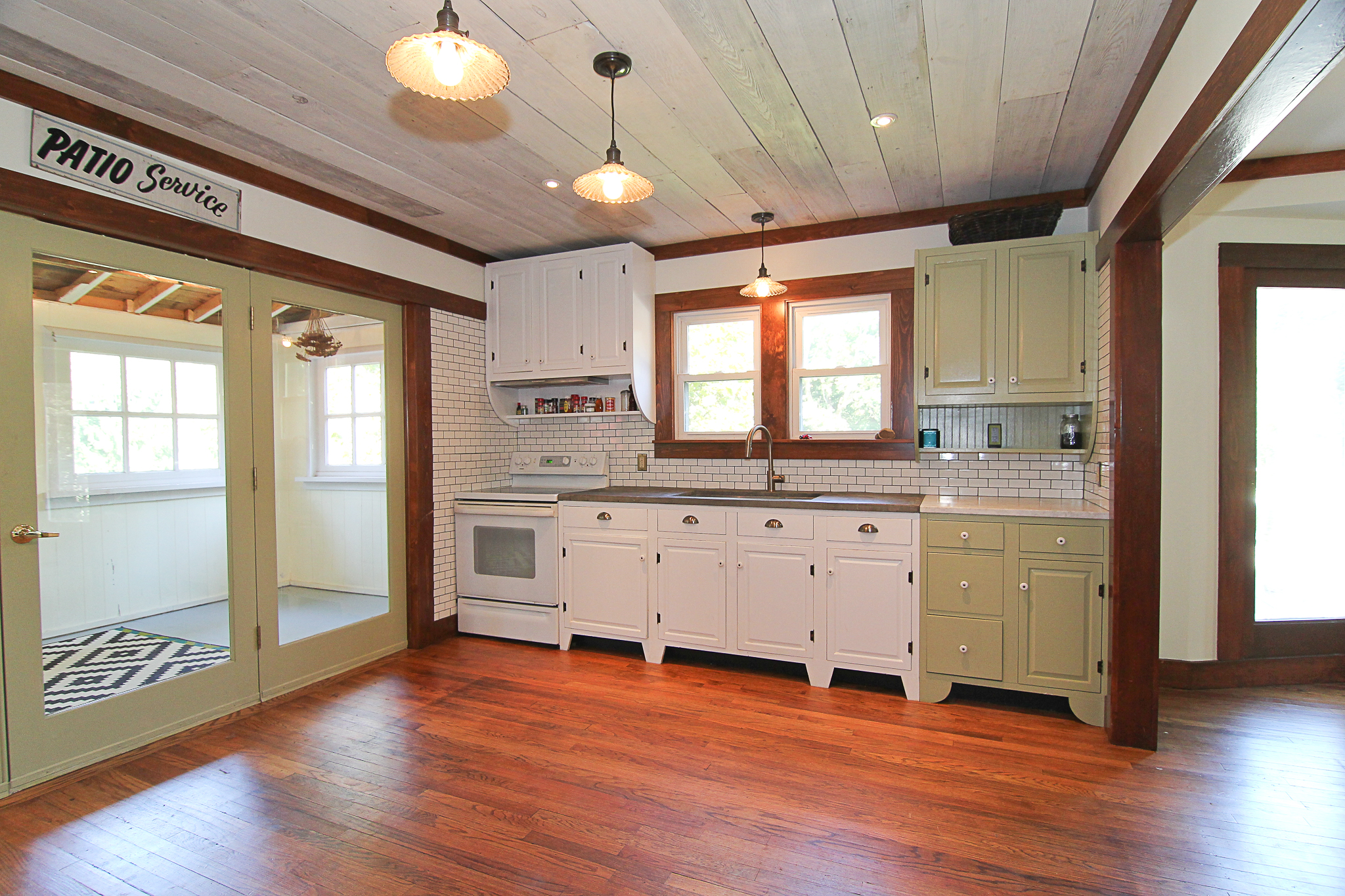 Does this kitchen look new? Airy Kitchens painted existing cabinets, refinished existing floors, used reclaimed wood for molding and ceilings, and purchased the glass doors at a salvage shop.