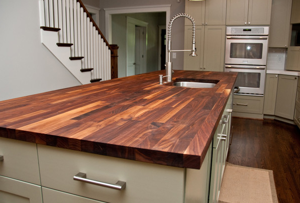 Butcher block counters add warmth to painted cabinets.