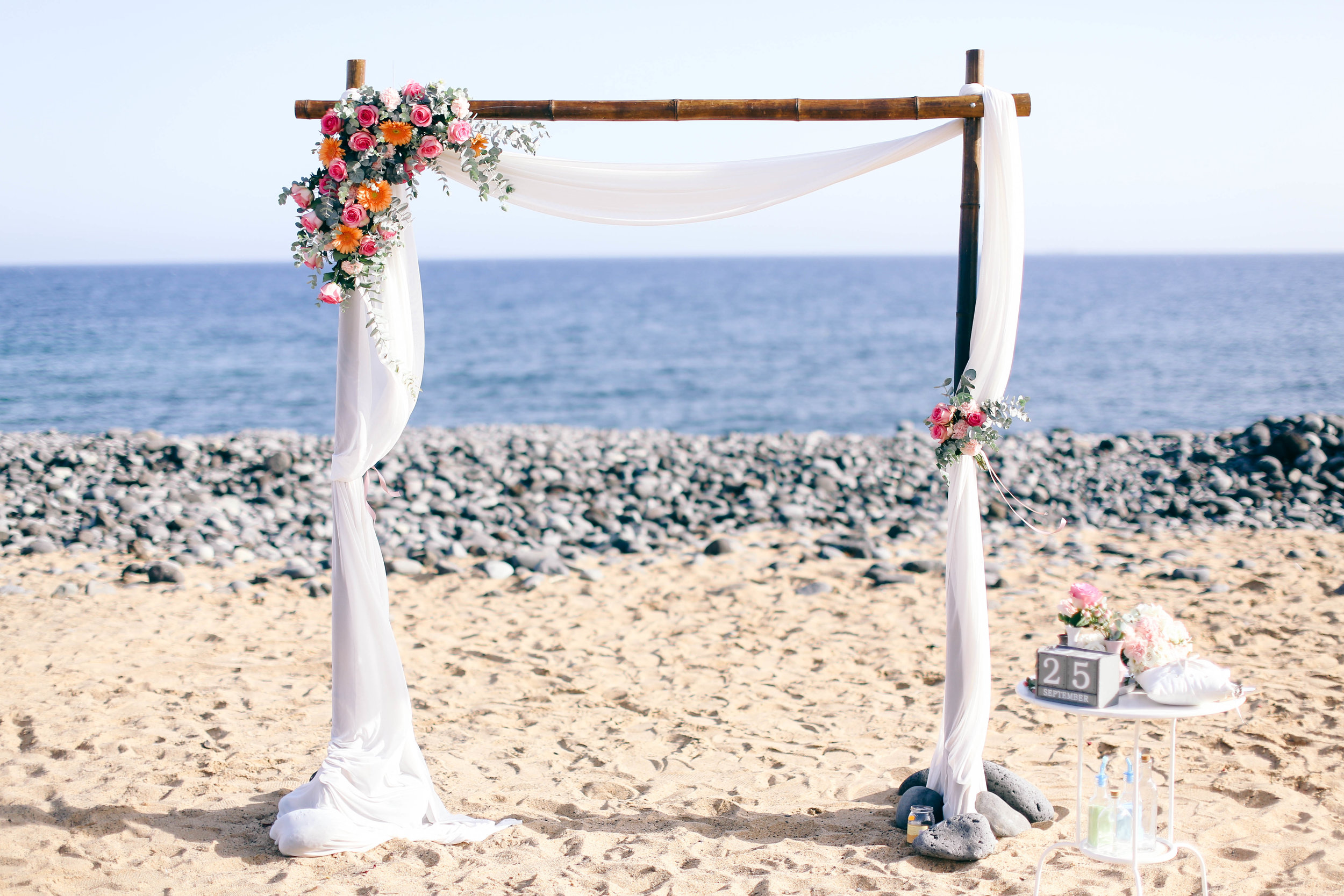 Beach ceremony and bamboo arch with basic flowers decor