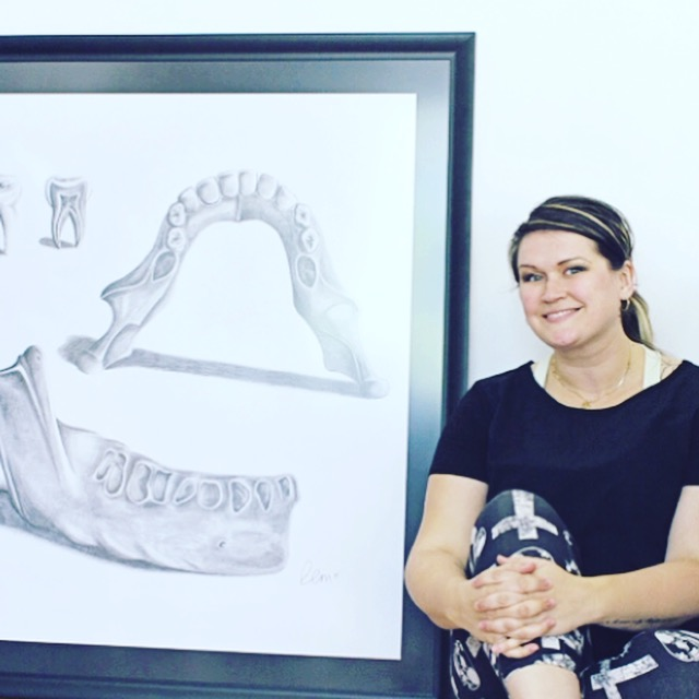 Robyn, now in her 30s, likes to draw and works as a tattoo artist. She sits beside a piece of her art. (Photo courtesy Robyn Marshall)