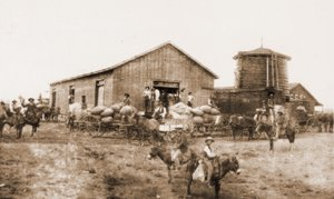 Clayton Commercial Company. The photograph of this wool warehouse is dated 1891. The warehouse is across Front Street from the Clayton Police Department. The wooden water tank that served only the railroad steam engines and the C.C.C.'s store warehouse no longer exist.