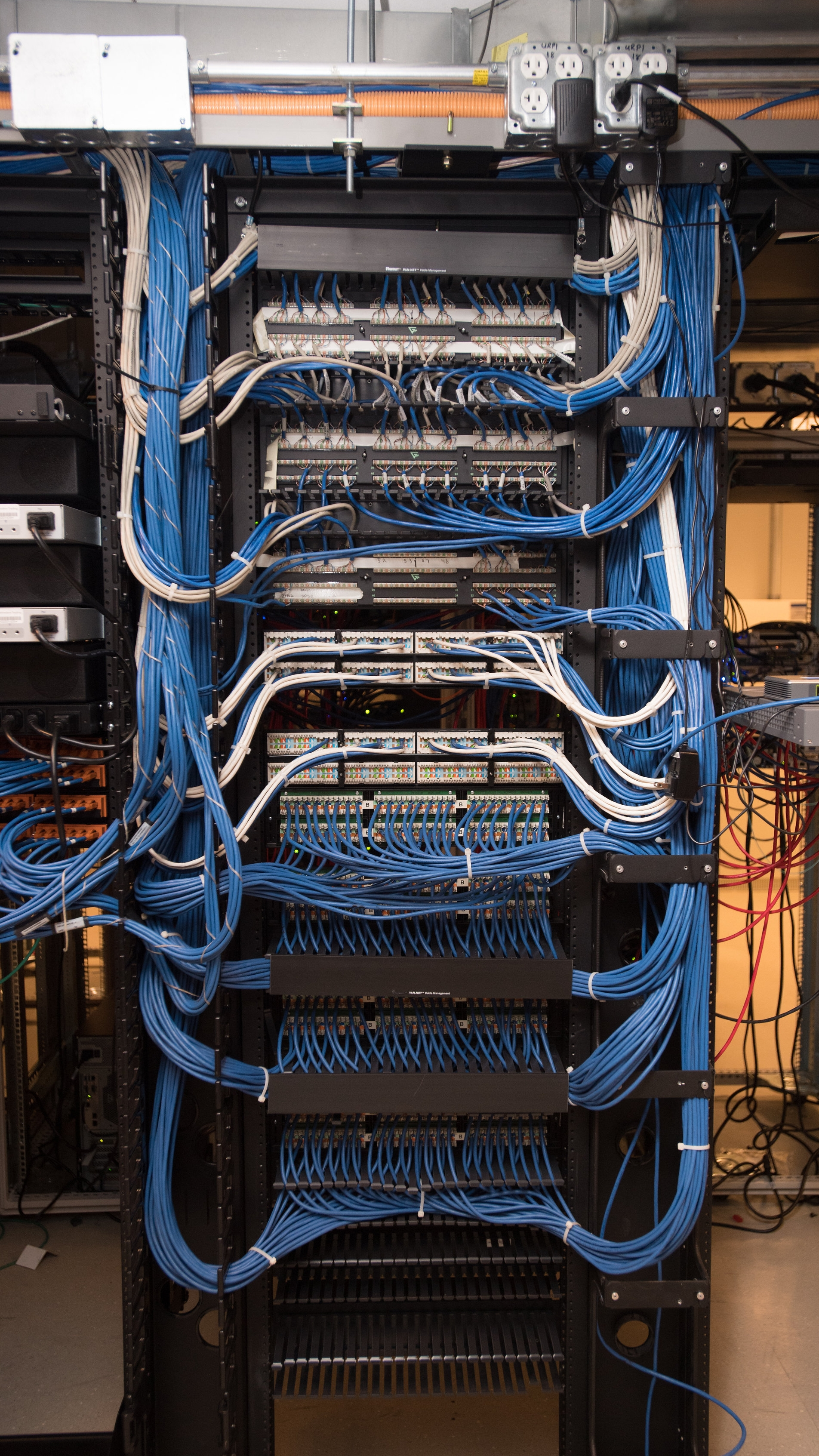 Photo of a computer server room with lots of wires
