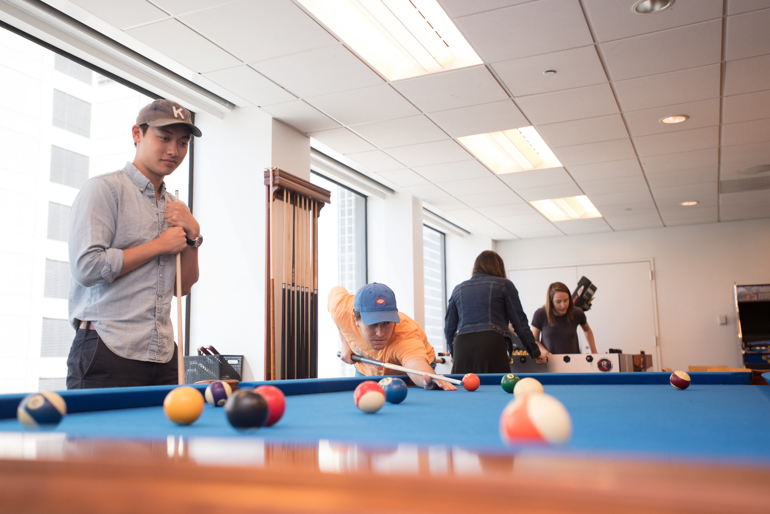 People playing pool in a game room.