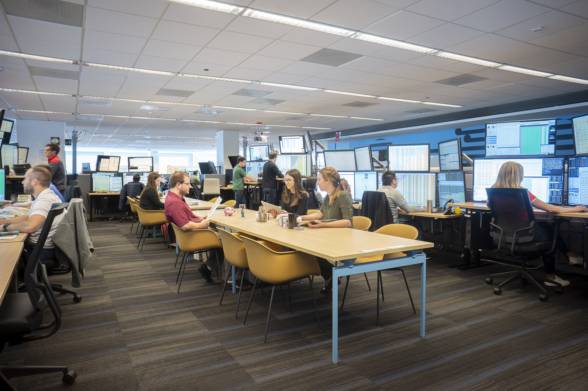 A view of one of the trading pods (or group of desks) in the Belvedere office. Some employees work in tables in the center while others sit at their desks around the perimeter.