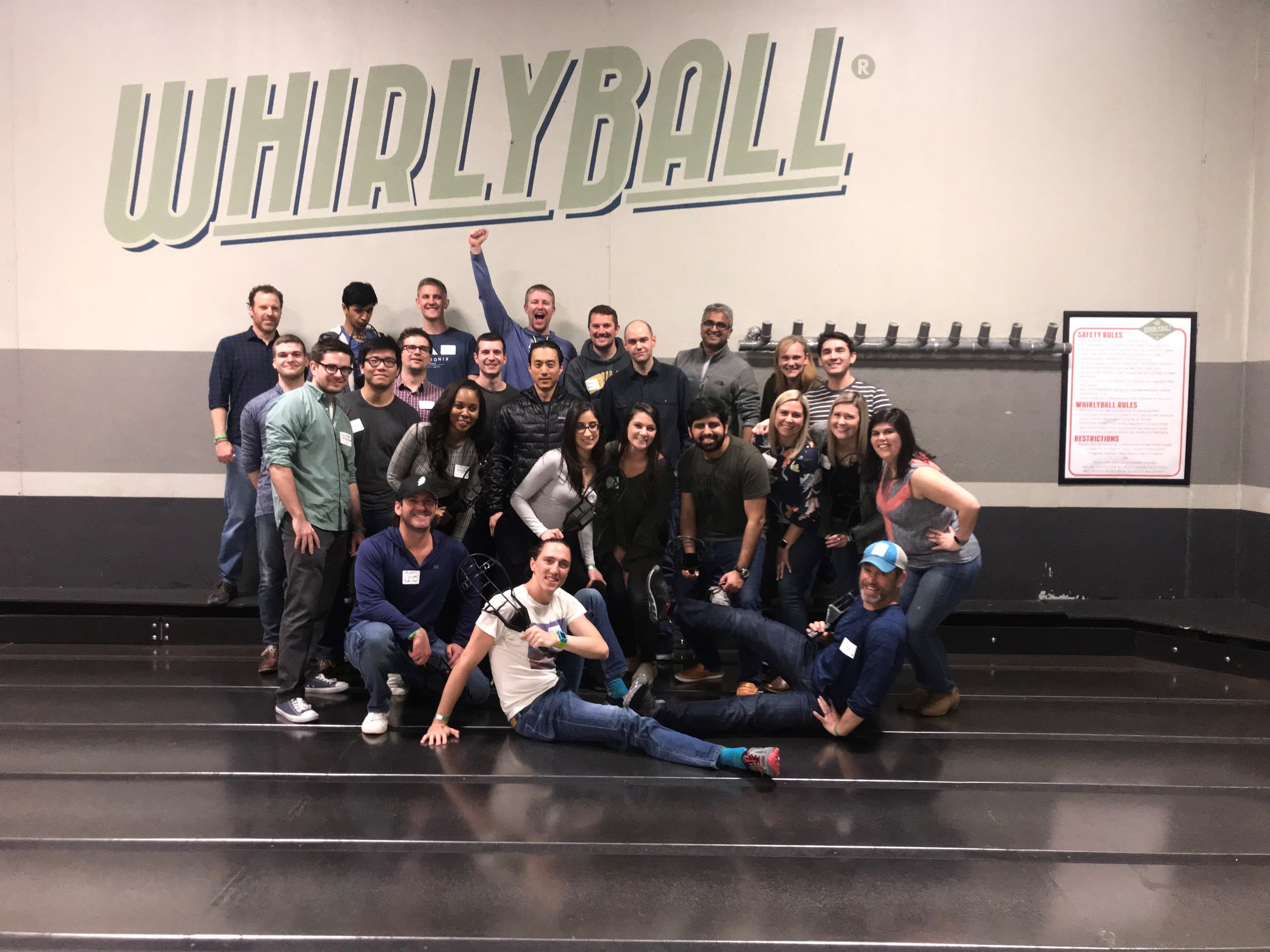 A large group of employees posing for a group photo at a Whirlyball new hire event