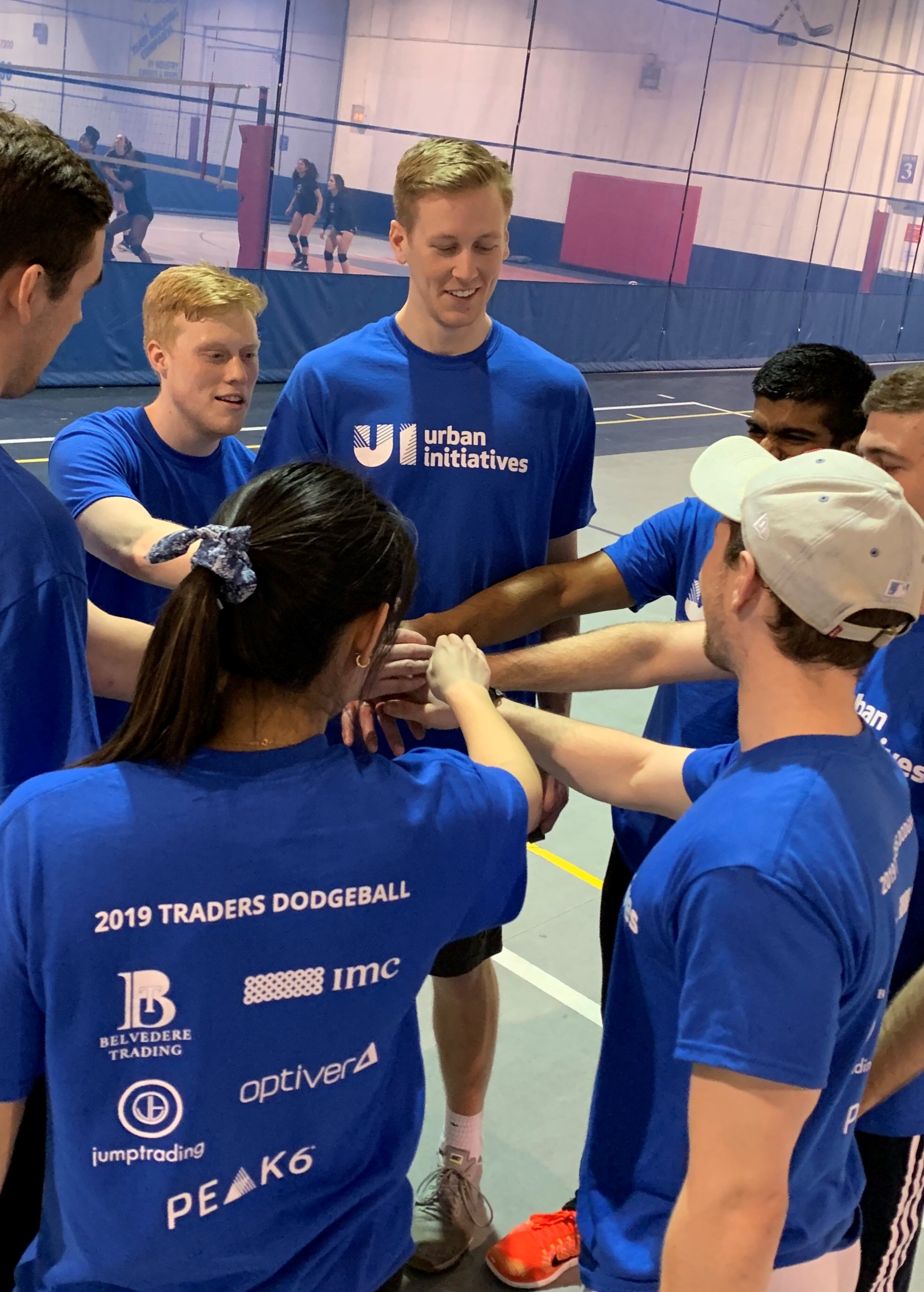 Team Belvedere with hands in the center of a huddle wearing Urban Initiatives t-shirts in preparation for a charity dodgeball tournament.