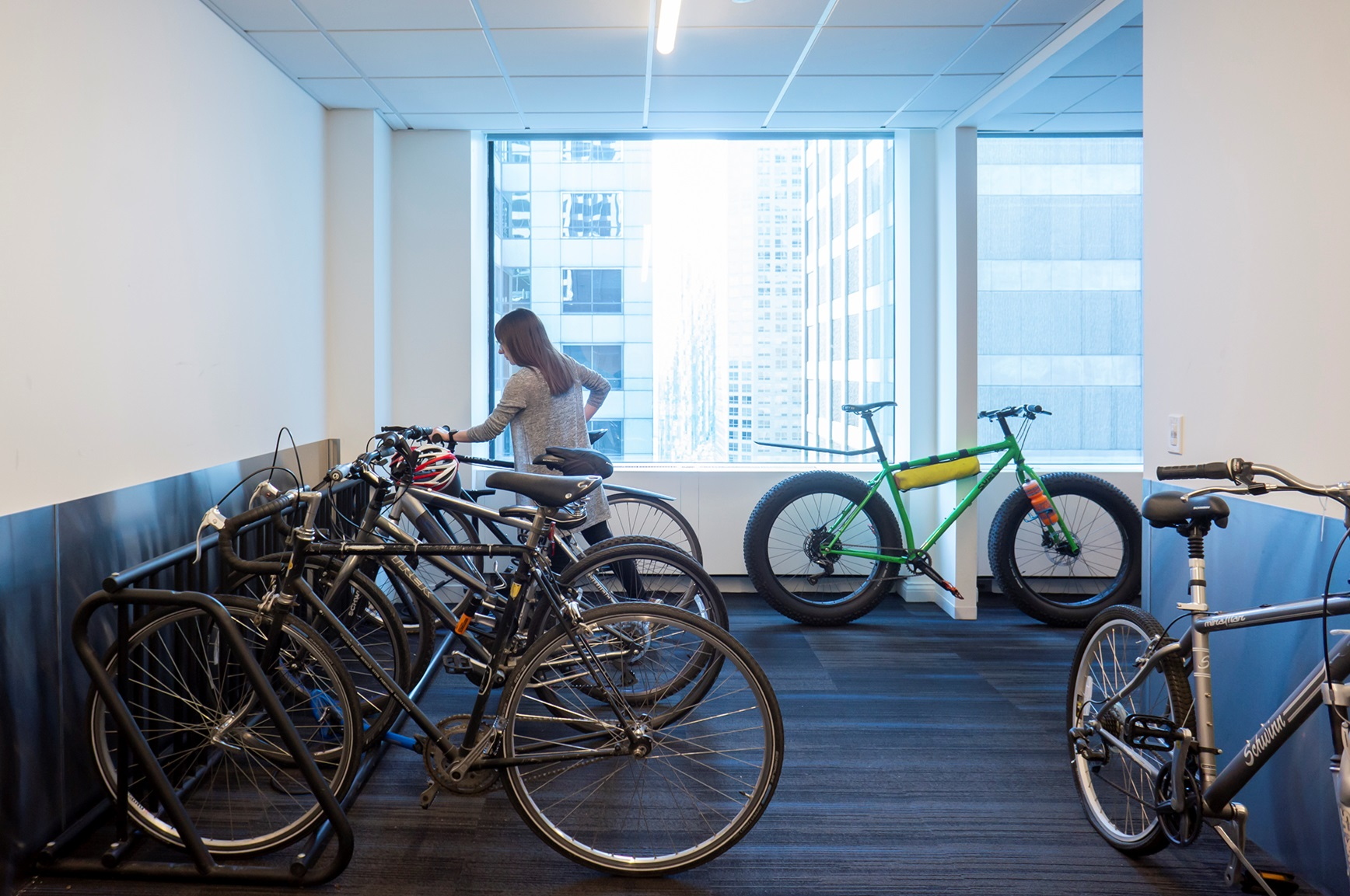 A woman stores her bike in the in-office bike storage room.