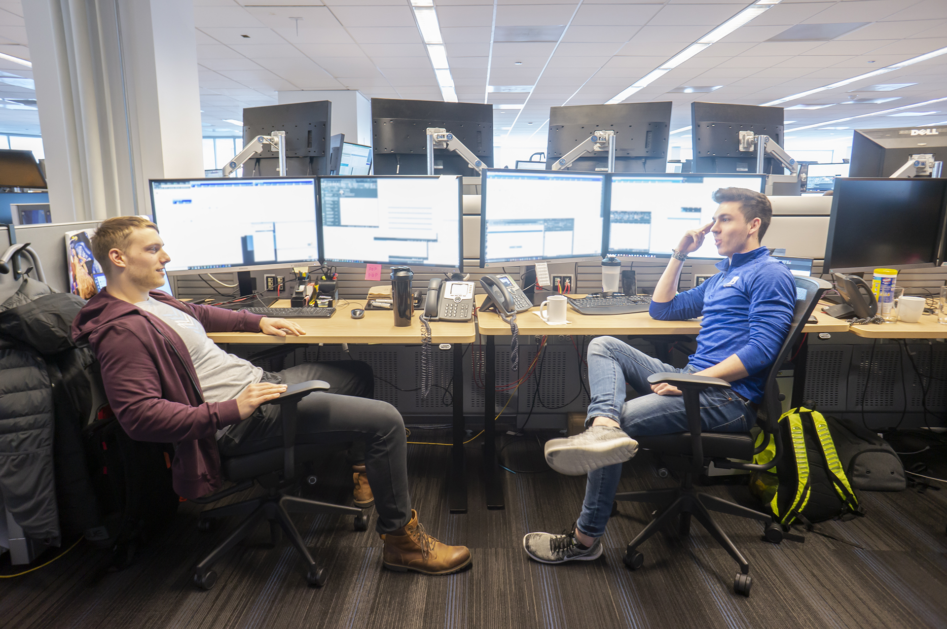 Photo of two people having a conversation at their desks.