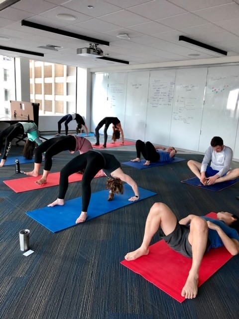 A group of people doing in-office yoga