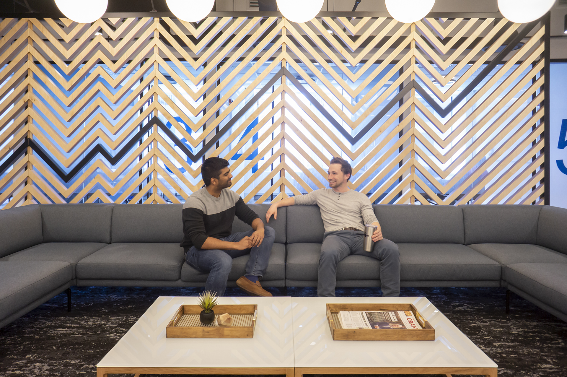 Two people sit and talk on a stylish couch. A zig-zag accent wall is behind them.