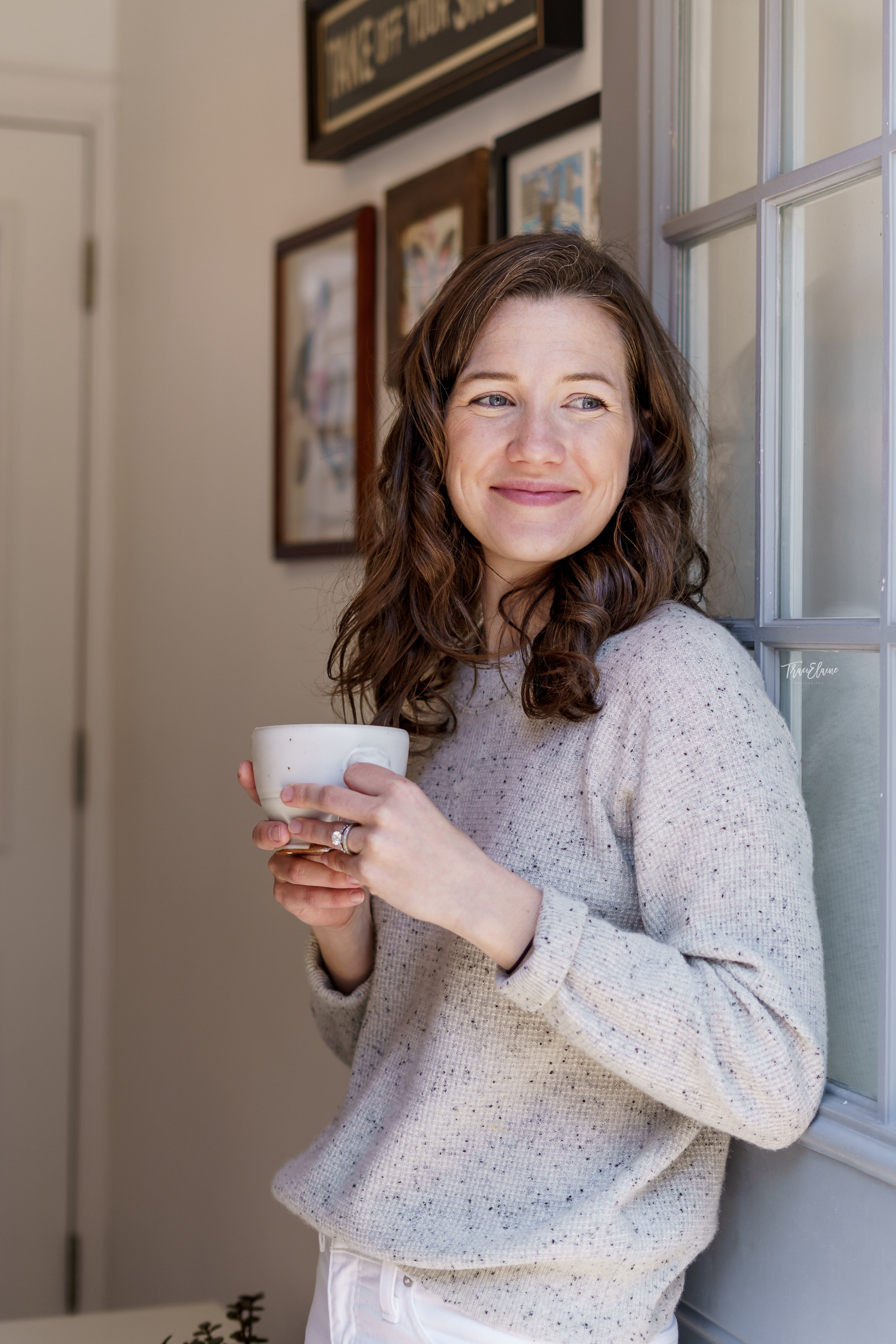 branding image, woman looking outside, woman with coffee in hand, morning photo, woman standing against door