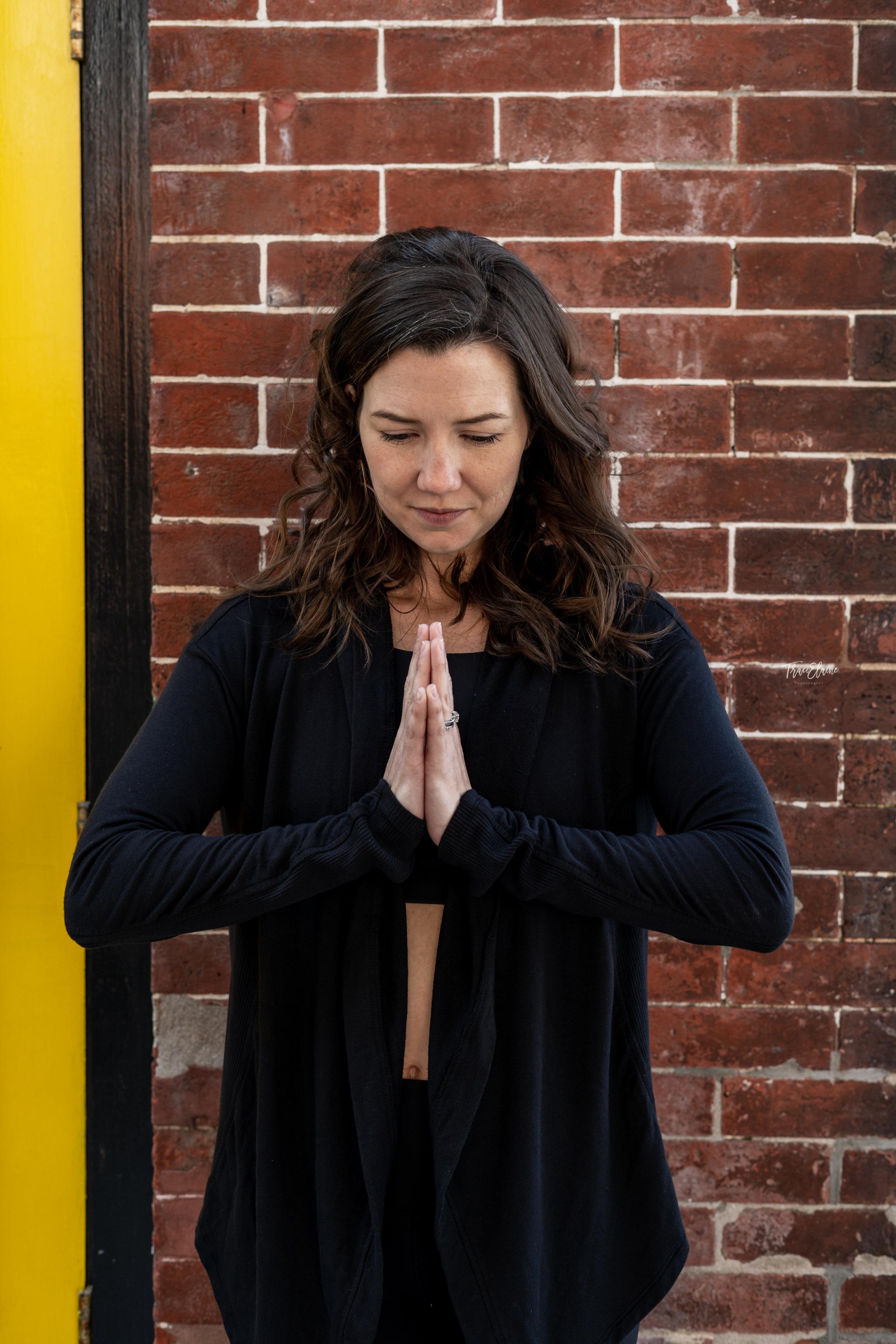 woman in yoga pose, woman meditating, woman against brick wall