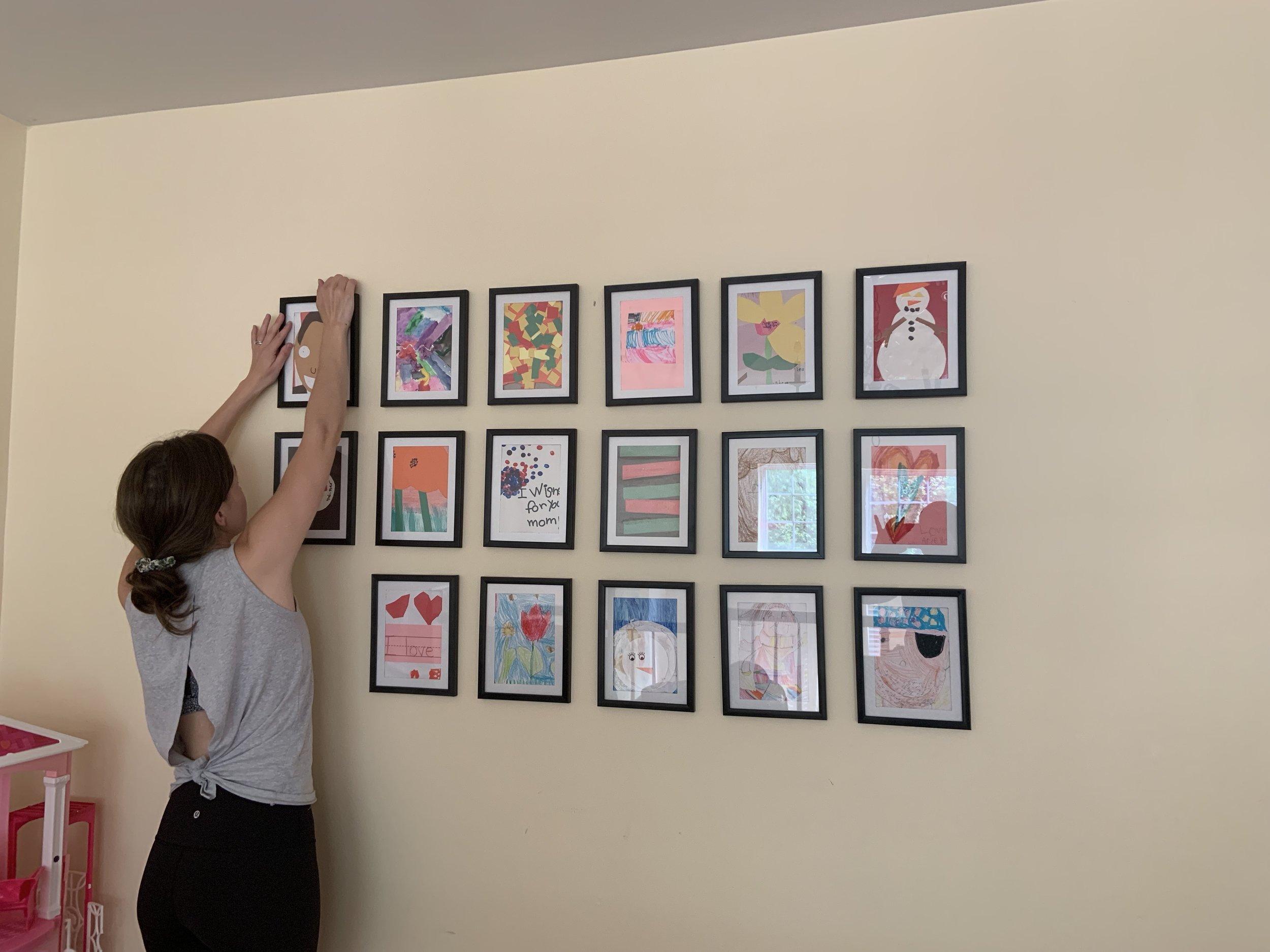 woman putting up Frames; gallery wall; kids artwork gallery, dollar store frames