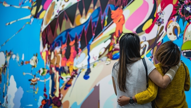 two individuals backs with their arms wrapped around each other staring at a bright and colorful mural on the wall.