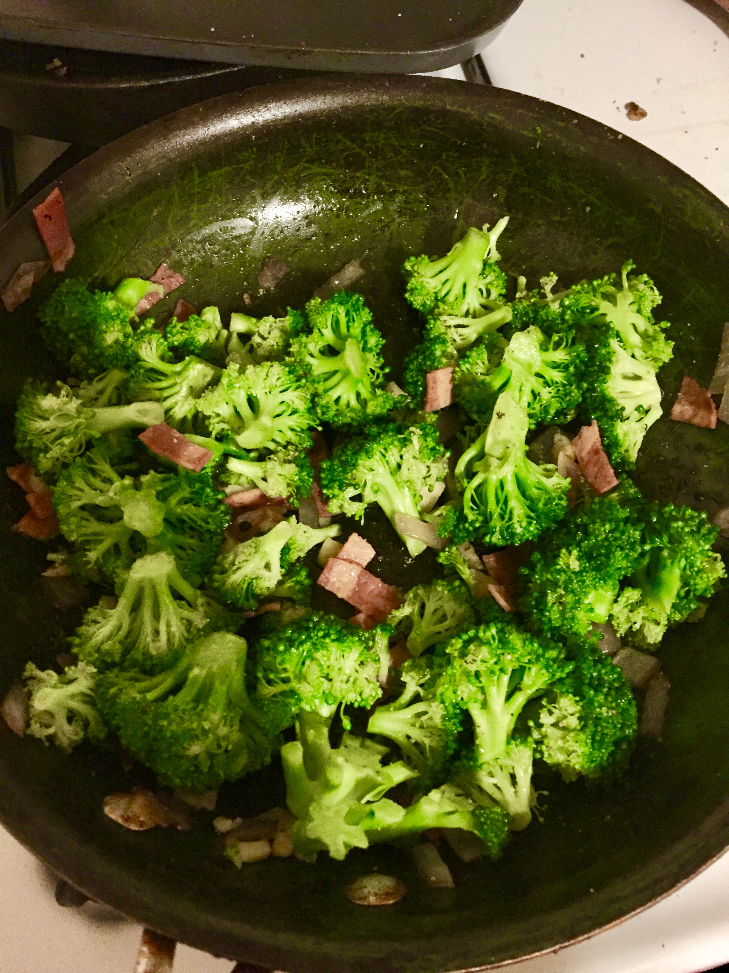 Add broccoli to the saucepan with the onions, garlic, bacon, and olive oil. Season the mixture with salt and pepper and set aside to cool.  When it is cooled, add diced cheddar cheese and 3 tbls of red wine vinegar.  Serve chilled and you'll elicit smiles, even if you're wearing clothes.