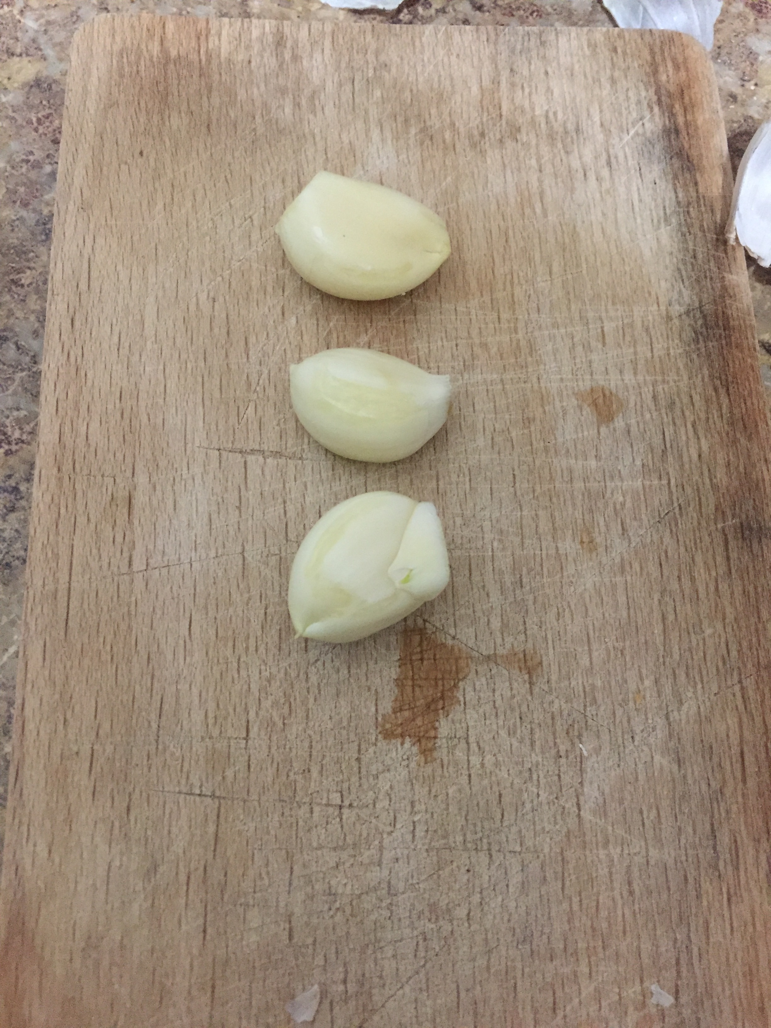 Dice the garlic cloves and add to a skillet coated in olive oil on medium heat, being careful not to overcook or burn.