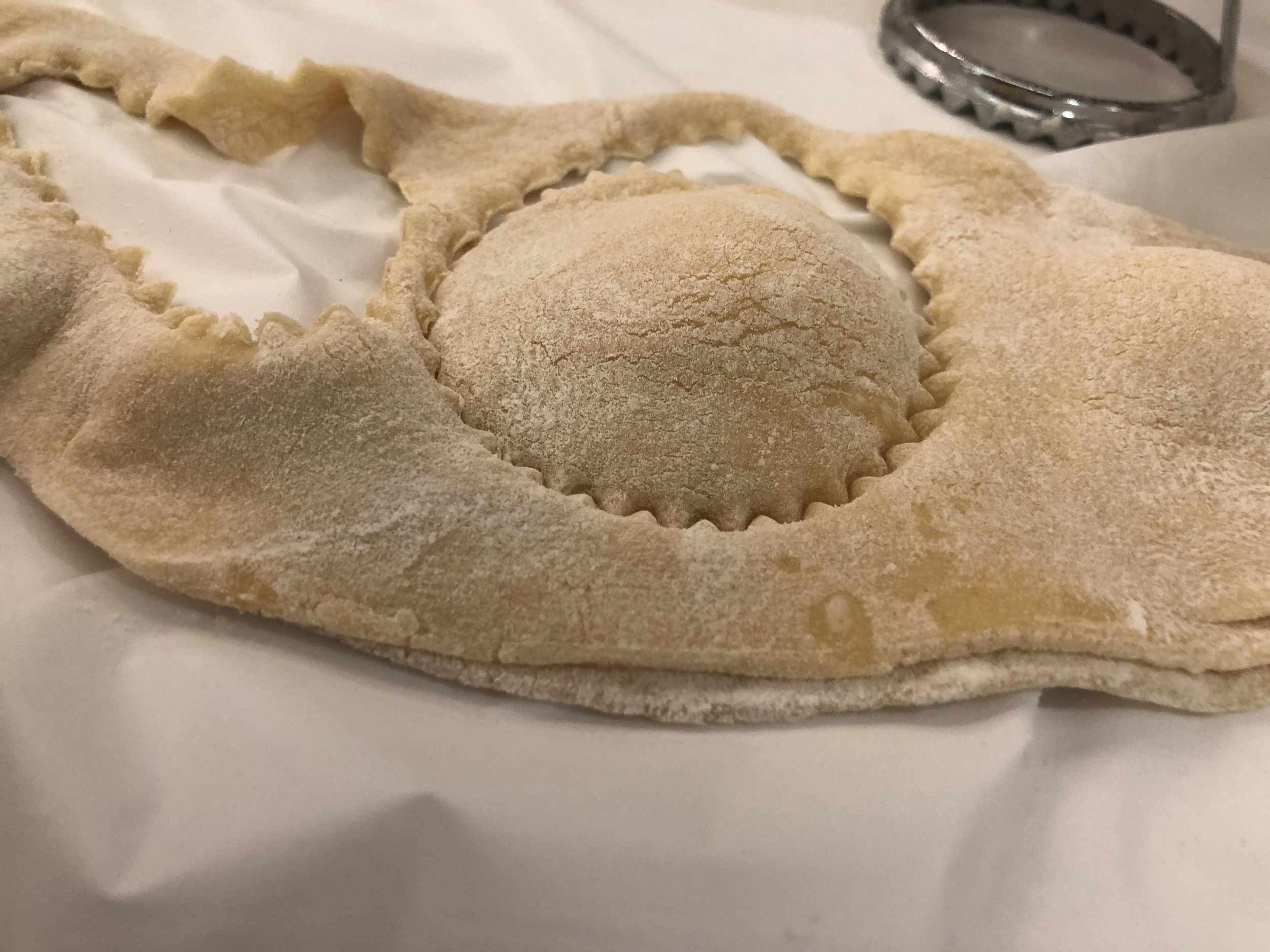 Fold the dough over so the filling make little mounds. Using your Ravioli cookie cutter, make individualized raviolis. Use your hand press around the filling of each, making individual raviolis.