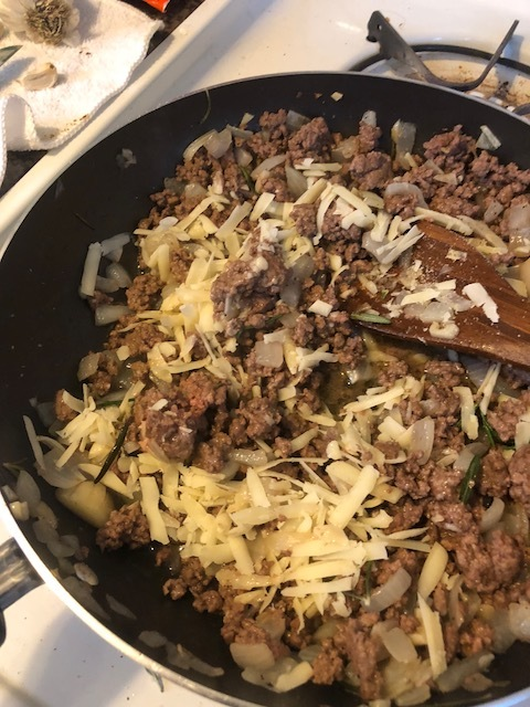 When beef is cooked through, add the onion powder, cinnamon, nutmeg, powdered garlic, salt and ground pepper. Mix throughly and taste. Add more of everything you think you should after tasting the meat.  Add the shredded parmesan and the ricotta. Turn off the heat and mix throughly.