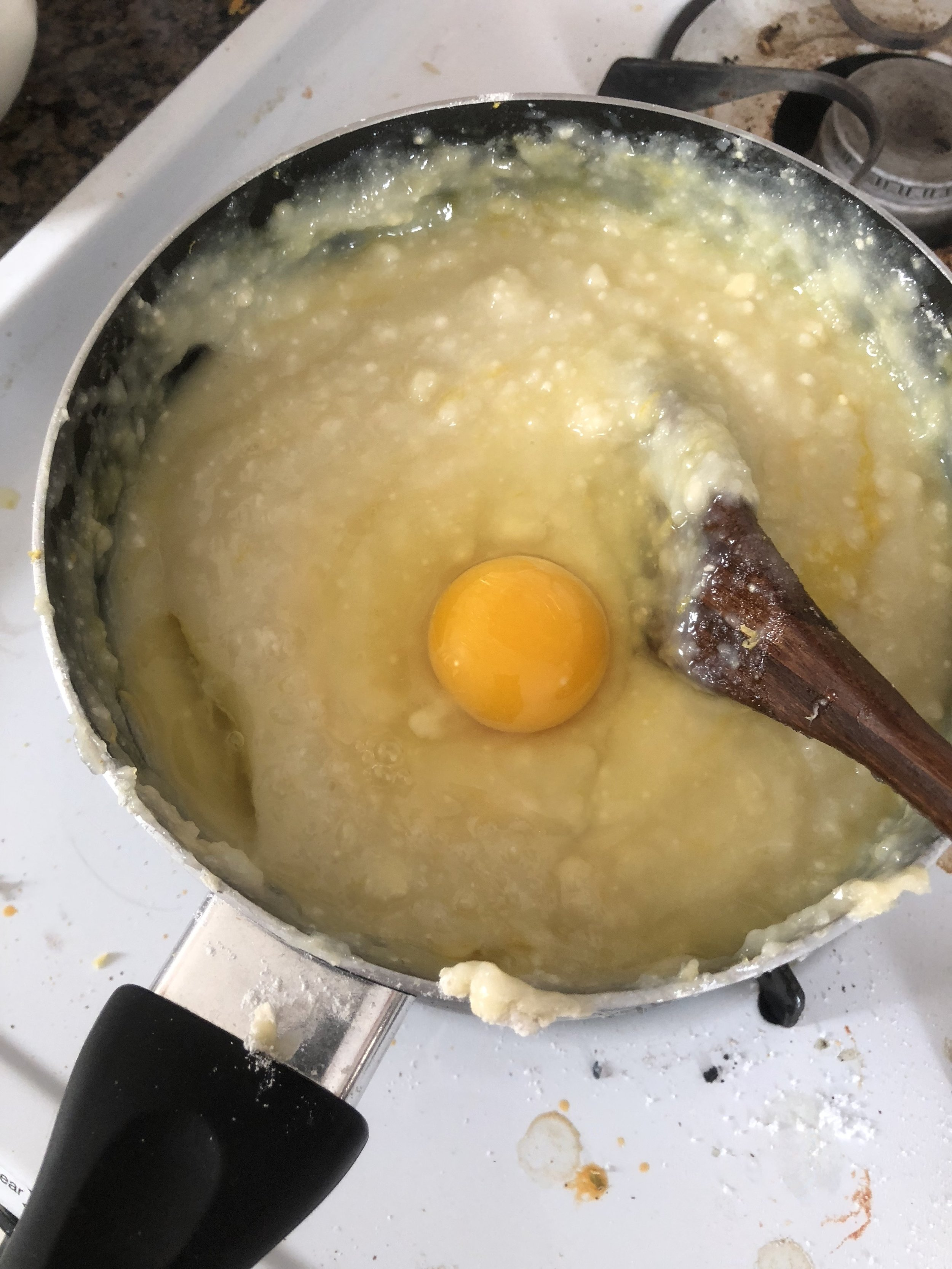 Put the the batter to a bowl to cool it down to warm, stirring frequently to prevent a skin from forming. Add eggs when the mixture cools (if you add the eggs earlier they'll cook in the hot bath of the mixture...