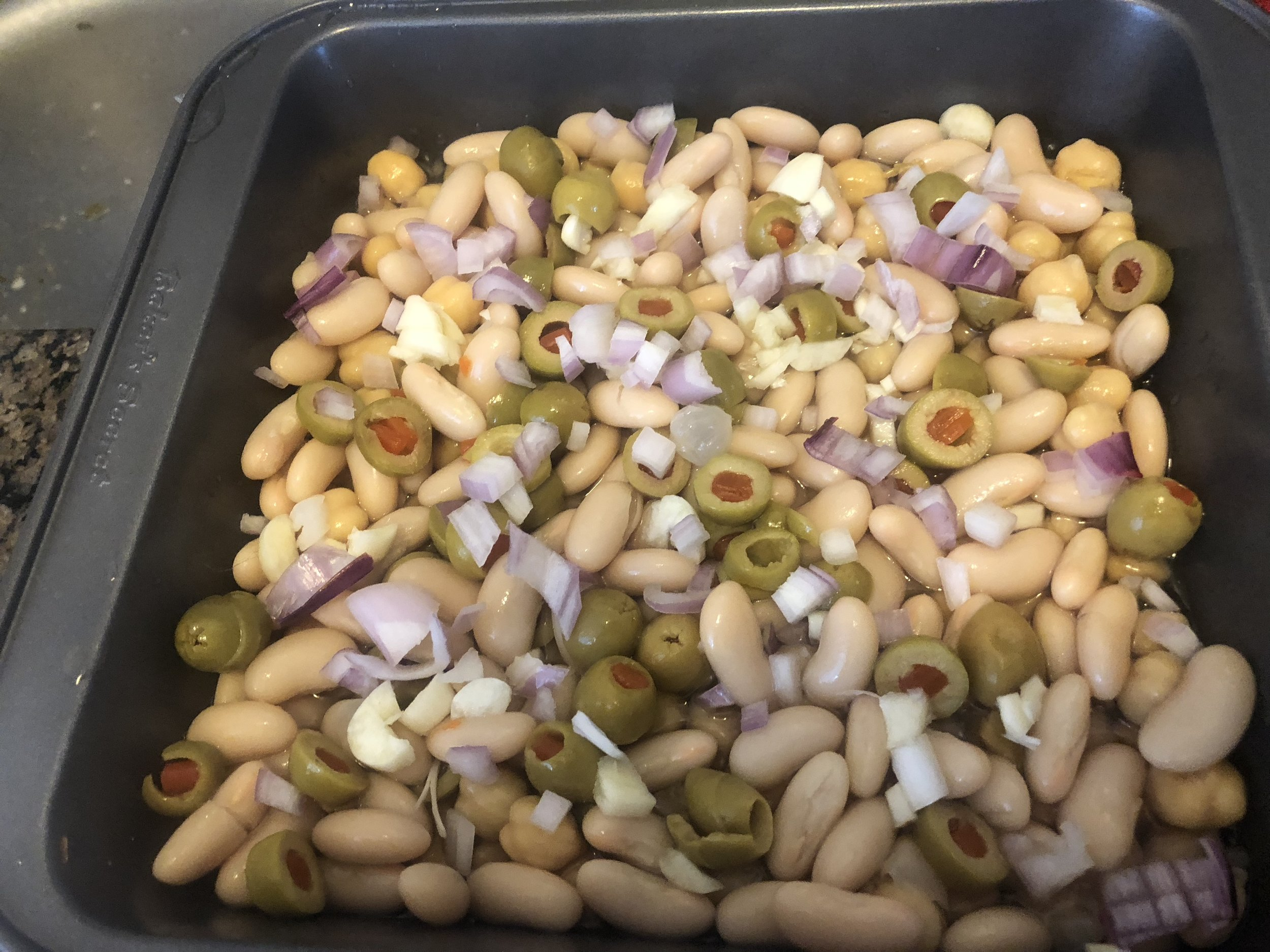 Preheat the oven to 325 degree  Mix the coined olives, shallots (with some reserved) and the beans and pour over the bottom of the pan. Pour in 0.25 cup of water